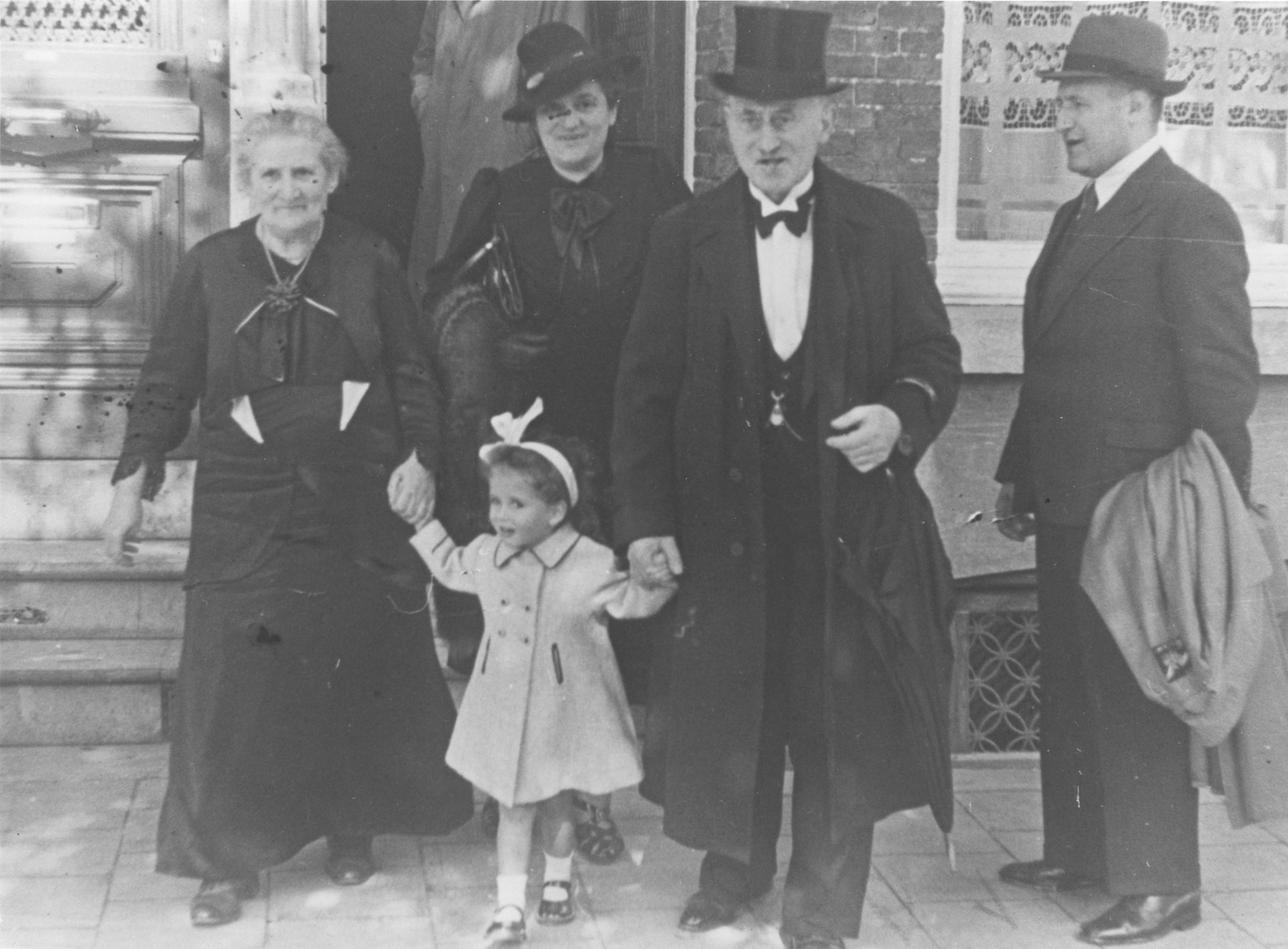 Elizabeth Reiss, a young Jewish girl, leaves a house accompanied by her maternal grandmother, Renee Rubens, great grandparents, and great-uncle, Jaap Trompeter.