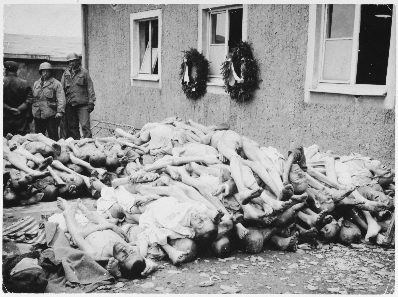 Two American soldier look at the piles of bodies stacked up behind the crematorium in Buchenwald.
