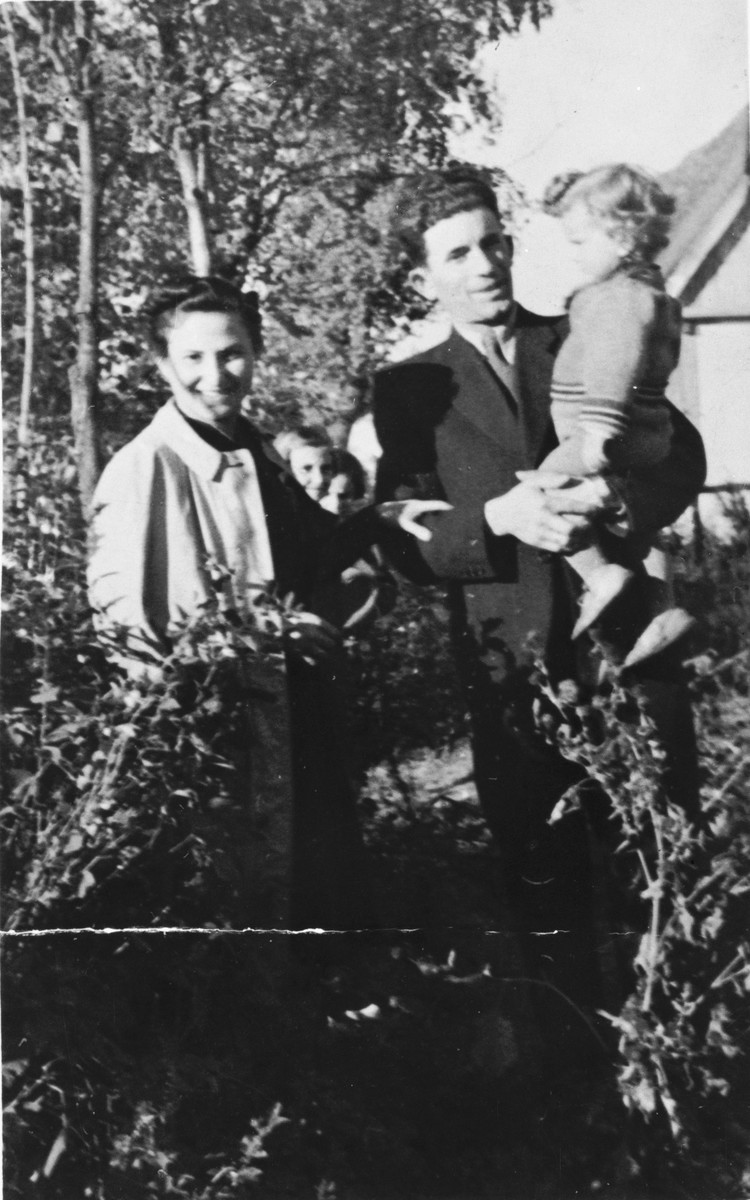 Bernard and Cesia Kaiser pose outside with their son, Jurek, in Chlewice after fleeing from the Kielce ghetto.