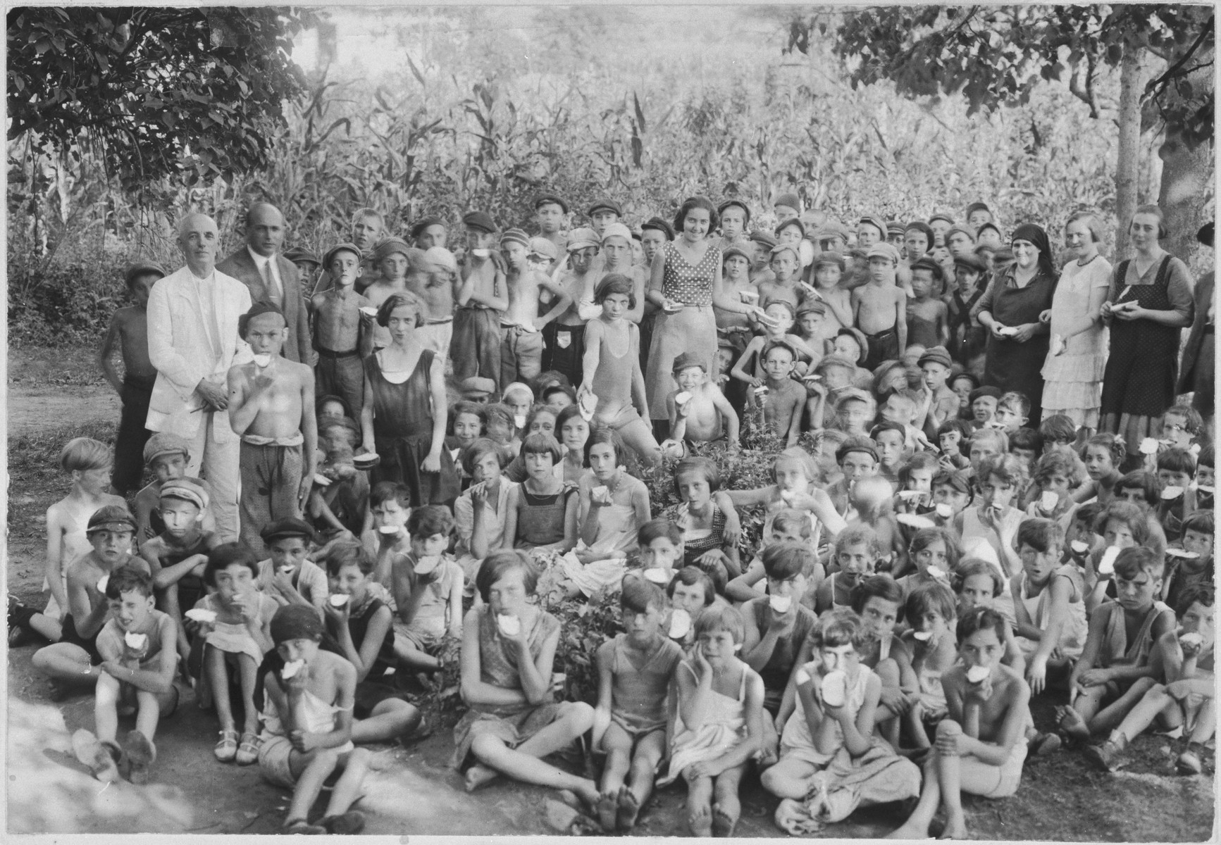Children eat a snack of bread and butter in a summer camp in Sighet for indigent children.  Among those pictured are Chaim Davidovics, Schlesinger, Arthur Roth, Leiby Taback, Hershel Schwartz and Laizer Eizikovics.