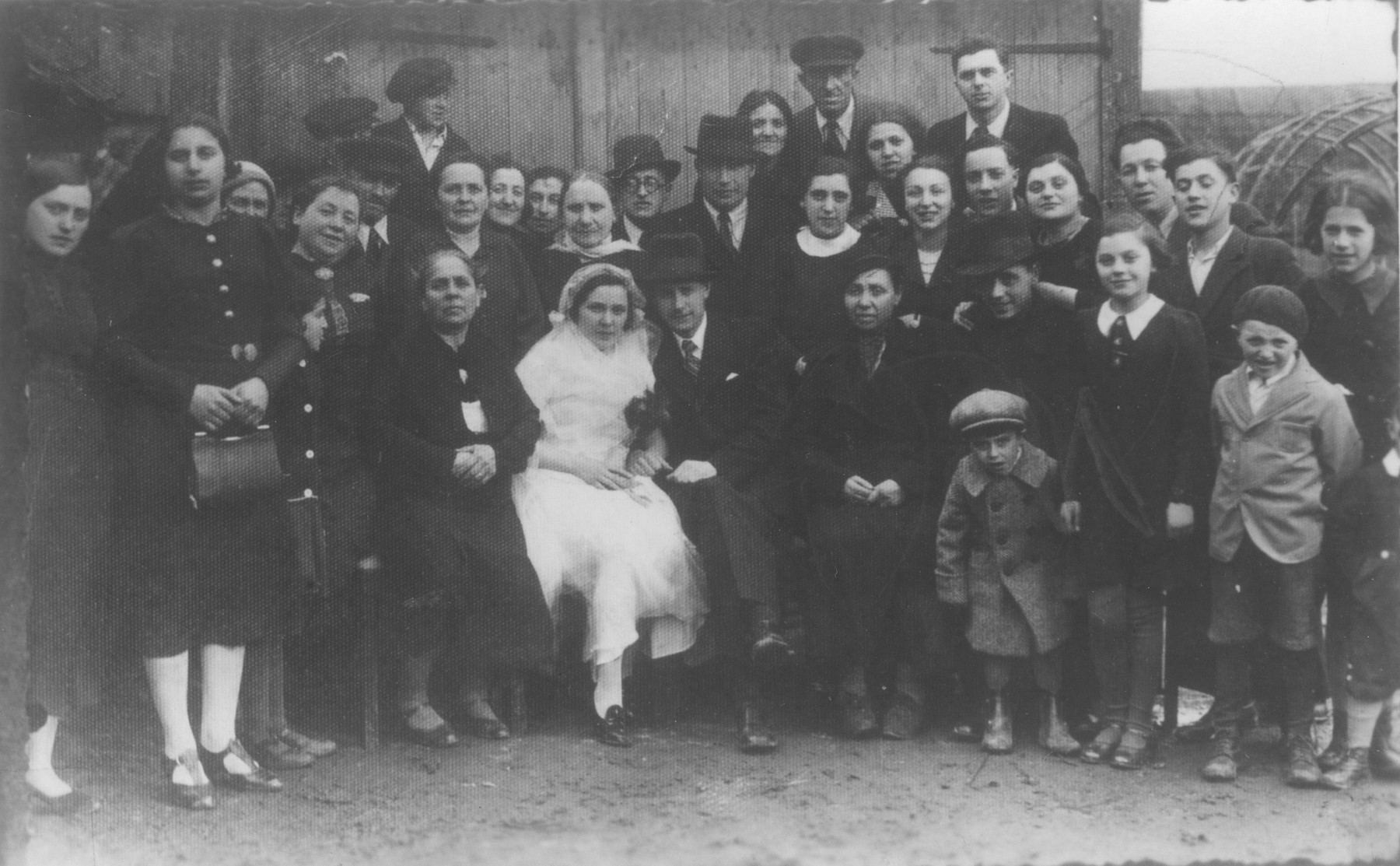 Family and friends pose with the bride and groom at a Jewish wedding in Telsiai, Lithuania.  The couple perished during World War II.