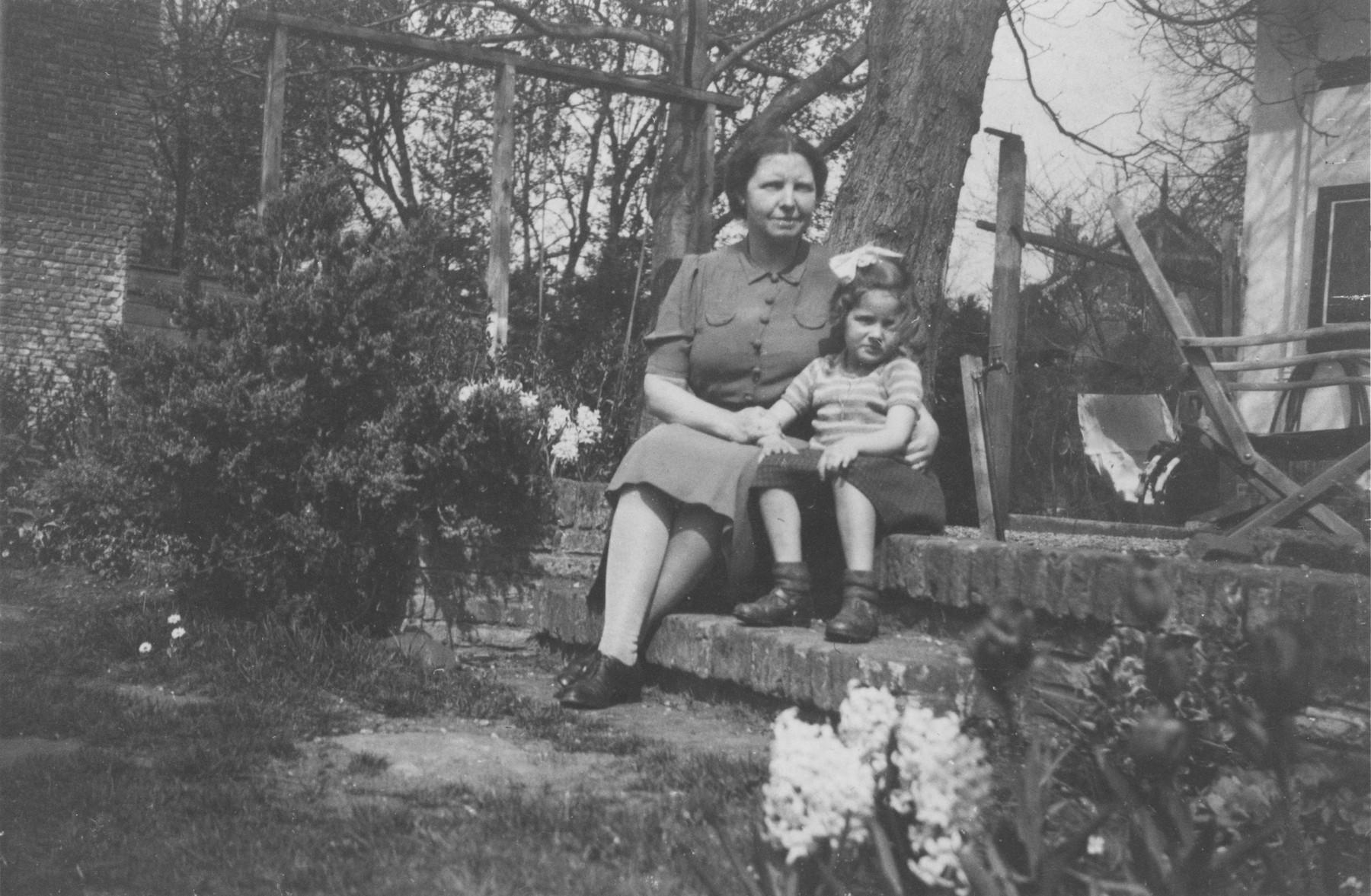 Dutch rescuer Wilhelmina Salters-Kloppenburg, sits on the steps outside her home with Elizabeth Reiss, a Jewish child she is hiding,