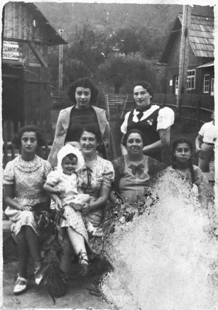 Sylwia Laufer sits on her mother's lap surrounded by her aunts.