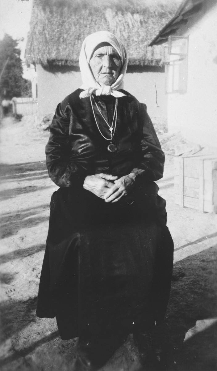 Yetta Beila Gutstein poses outside her home in the small shtetl, Ustye Zelenoye.