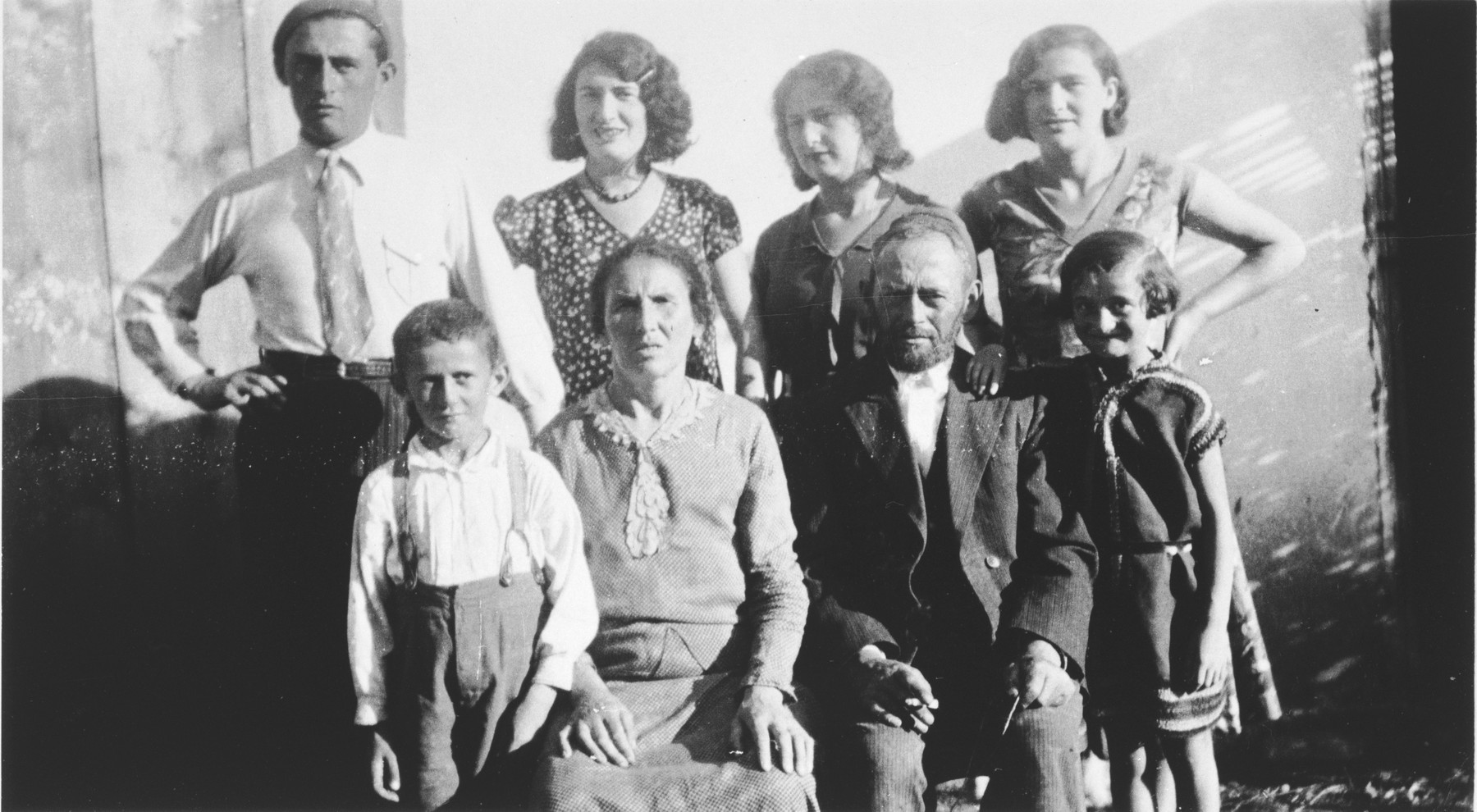 Rivka and Meshilem Frisch pose with their children outside their home in a small shtetl.  Standing from left to right are Yisroel, Fridjeh, Ruzie and Peshe.  Sitting are Dudie, Rivka, Meshilem and Mancha.  Only Fridjeh survived.