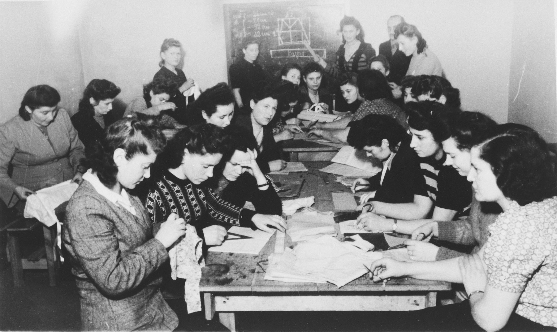 Women do hand sewing in an ORT vocational school in the Zeilsheim displaced persons' camp.  Among those pictured is Fayga Galas, on the left with her hand raised.