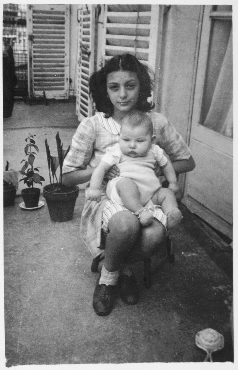 Brenda Hershkovitz holds her baby sister, Annie, on the balcony of their Paris apartment.