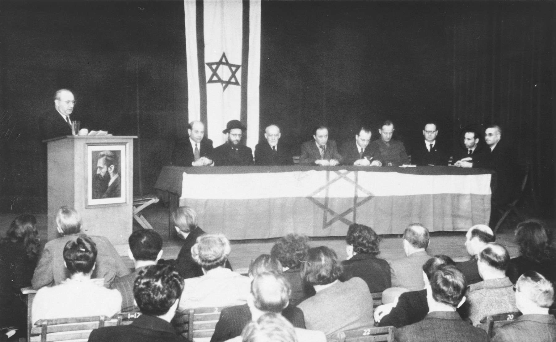 Zionist gathering of Jewish displaced persons in the British zone.  Those pictured include Mr. Yunis, Abraham Lipshitz, Norbert Wollheim, Roman Berger, Josef Rosensaft and [probably] Dr. Leo Baeck.