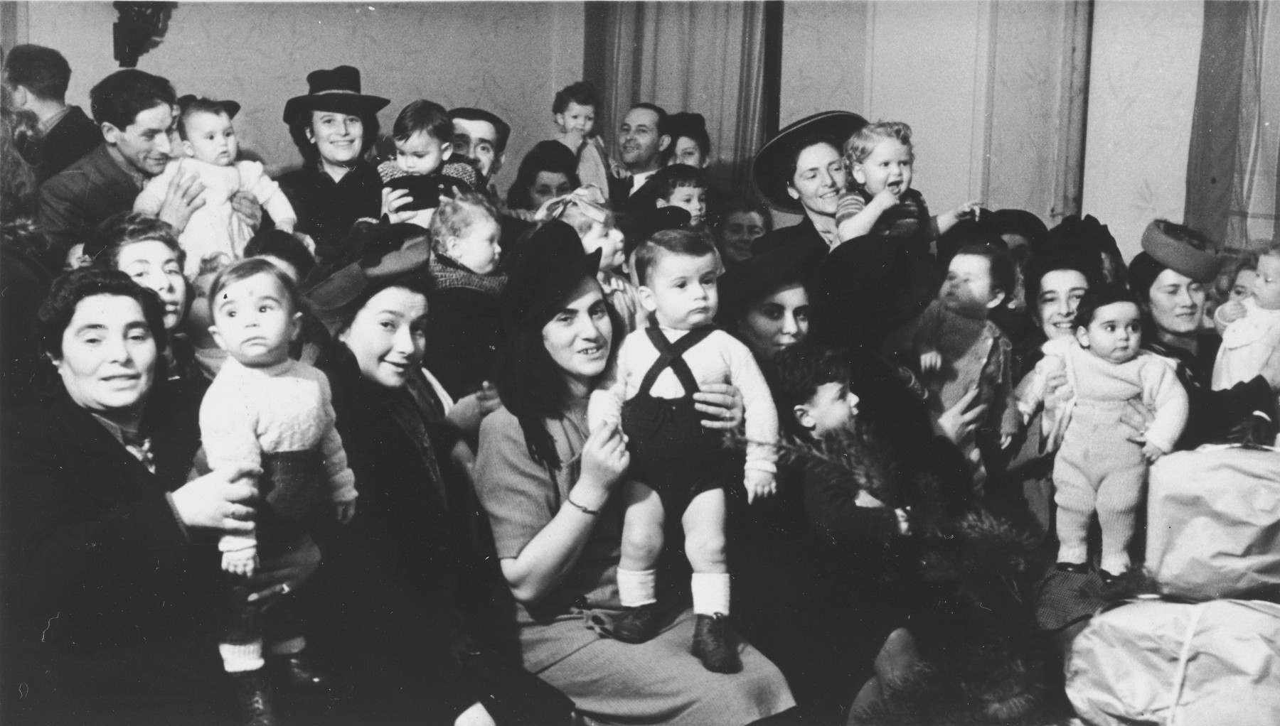 Women and children celebrate Tu B'Shvat in the Hanover DP community.  Among those pictured is Mrs. Roman Berger.  In the back center is Shimon Bornstein holding his son David.