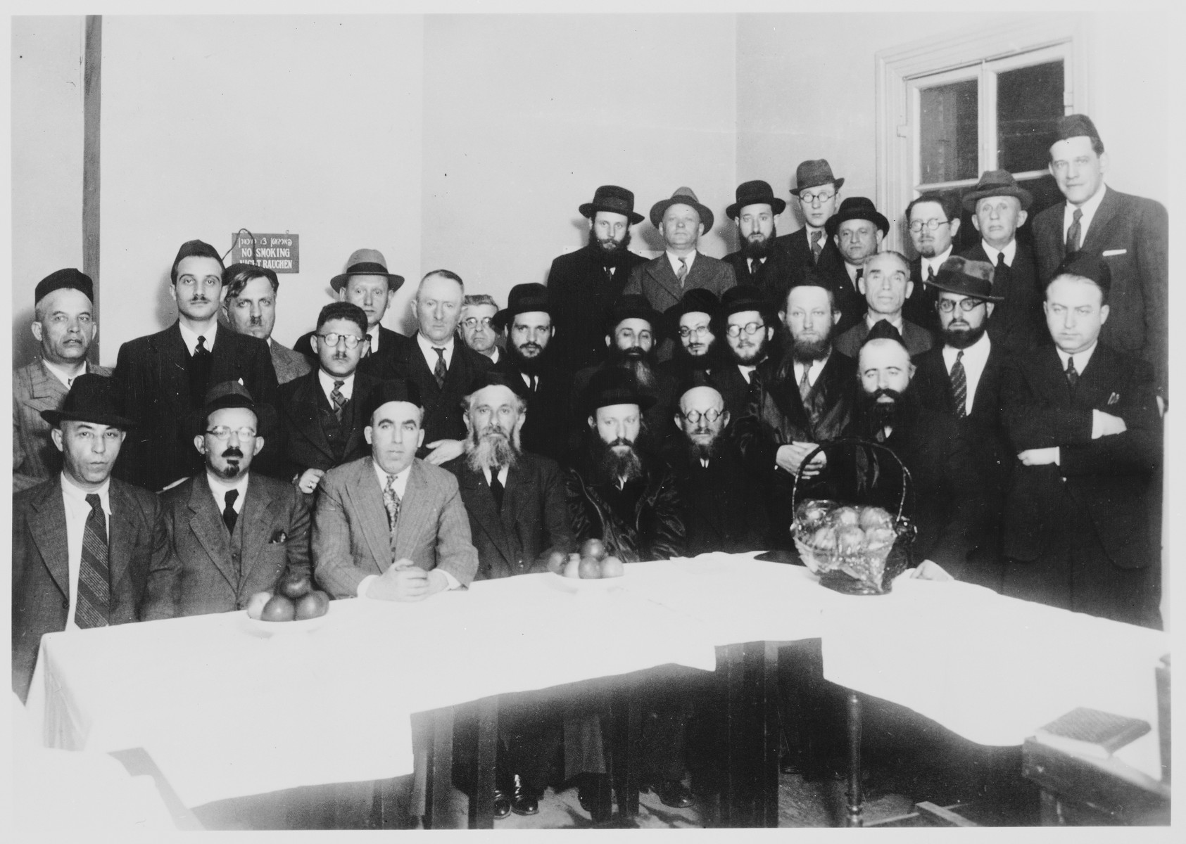 Group portrait taken of Jewish emigres, and religious Jewish refugees  who escaped from Europe with visas signed by Chiune Sugihara, in Kobe, Japan.  Joseph Ganger is seated in the first row third from the left.  Rabbi Shmuel Dovid Walkin is seated fifth from the left. Standing on the far left is Solomon Stolowy.  In the back corner, second from the left is Hirsh Marinski, a business partner of the Stolowy family.