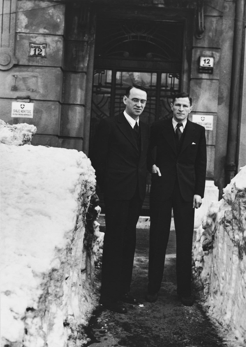Charles (Carl) Lutz (left) stands with his colleague, Mr. Steiner, outside one of the consulates in Budapest between two mounds of snow.
