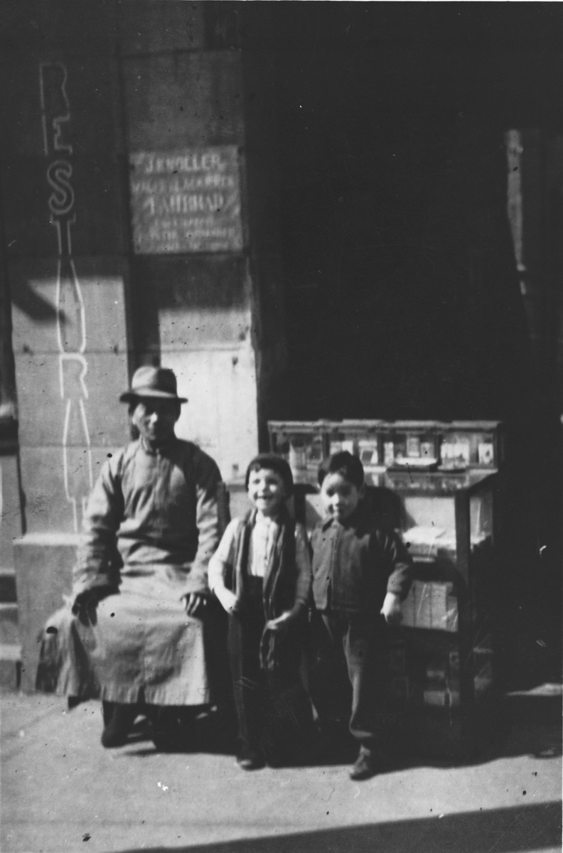 Two Jewish refugee children pose with a Chinese man on a street in Shanghai.  Pictured in the middle is Harry Fiedler.