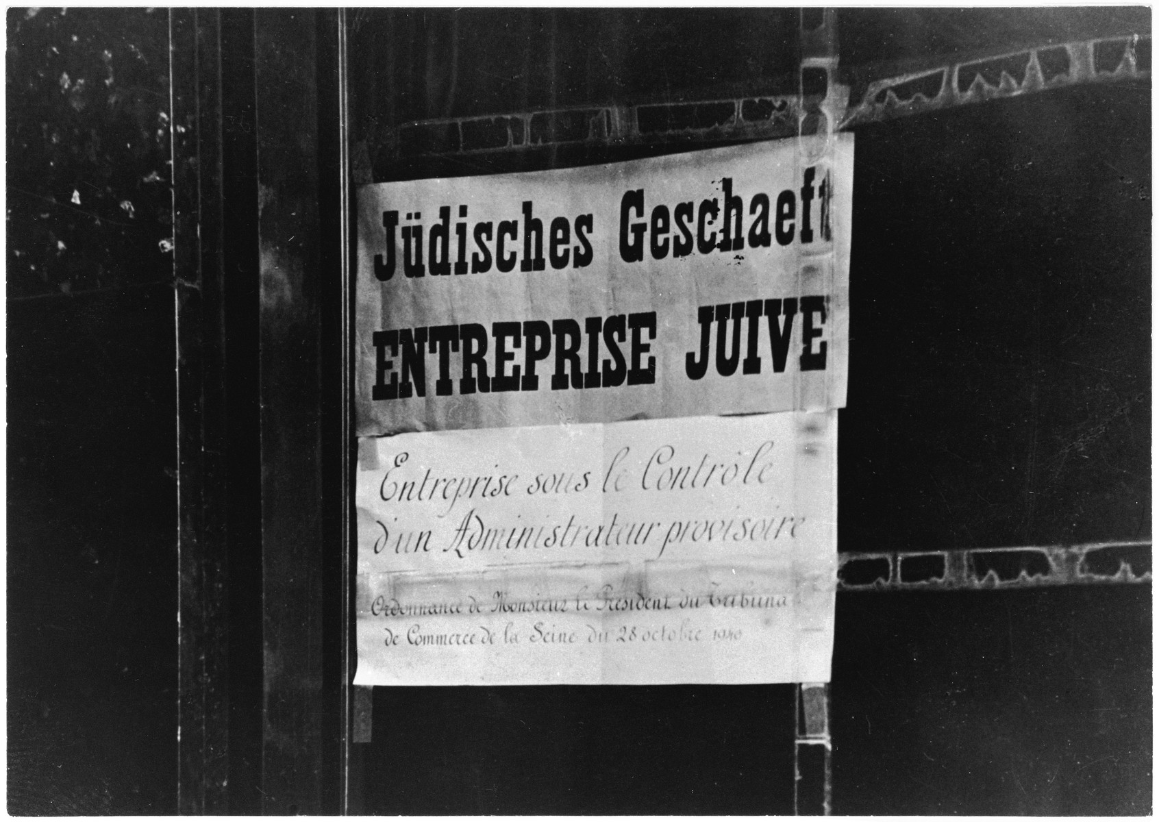 "A sign in German and French posted on a shop window reads ""Jewish business.""  A second sign below the first indicates that the business is under new, temporary management by order of the President of the court of commerce of the Seine."