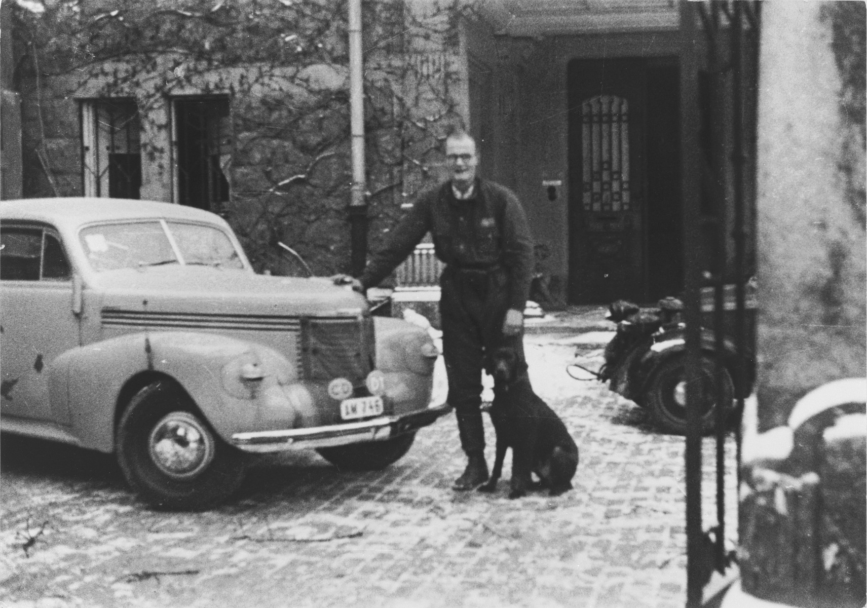 Lars Berg, a member of the Swedish legation in Budapest, 1944-45, poses with his dog next to a car.   Berg has been honored by Yad Vashem for his involvement in the rescue of Budapest Jews in the last year of the war.