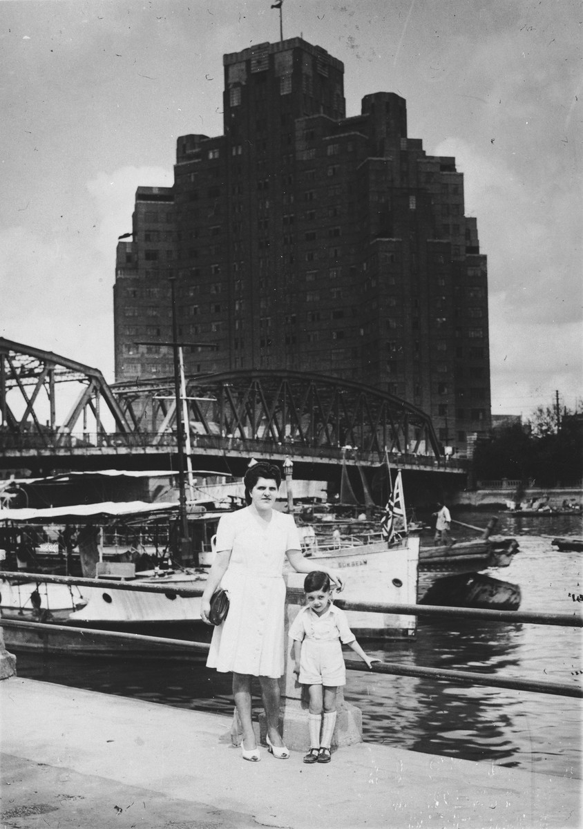 Berta Fiedler, a Jewish refugee from Vienna, poses with her son Harry on a bridge at the waterfront in Shanghai.