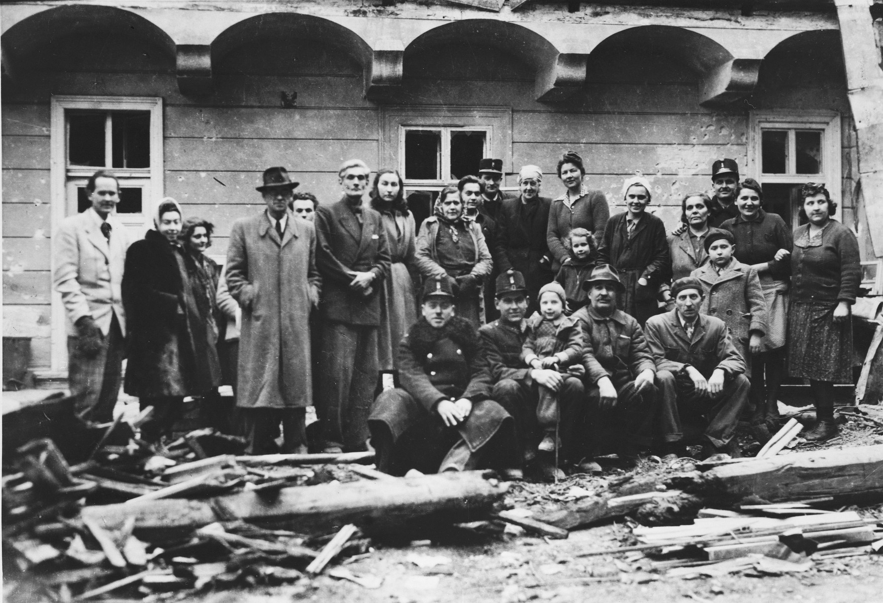 Charles (Carl) and Gertrud Lutz pose with police and former employees among the ruins of the British legation in Budapest after the liberation.  Among those pictured is Carl Lutz, his first wife, Gertrud, his future wife, Magda, and his future step-daughter, Agnes.