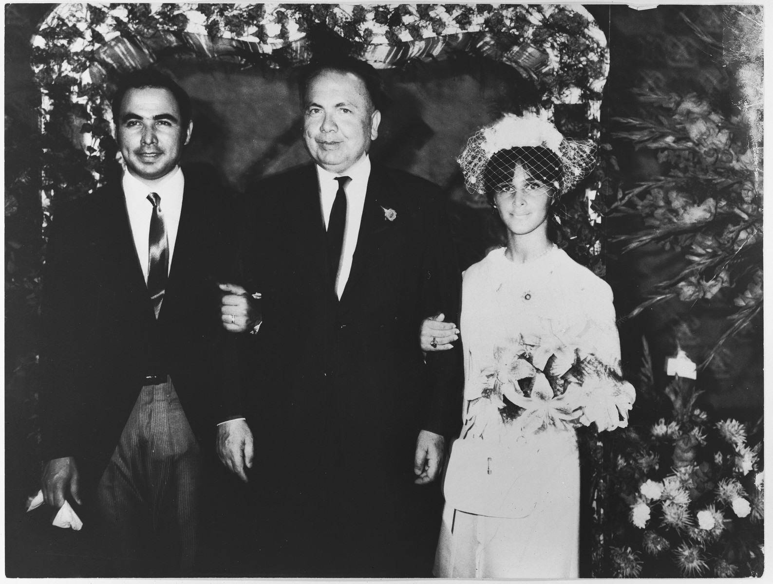 Turkish diplomat Selahatin Ulkumen poses with his son, Memet, and daughter-in-law at their wedding.