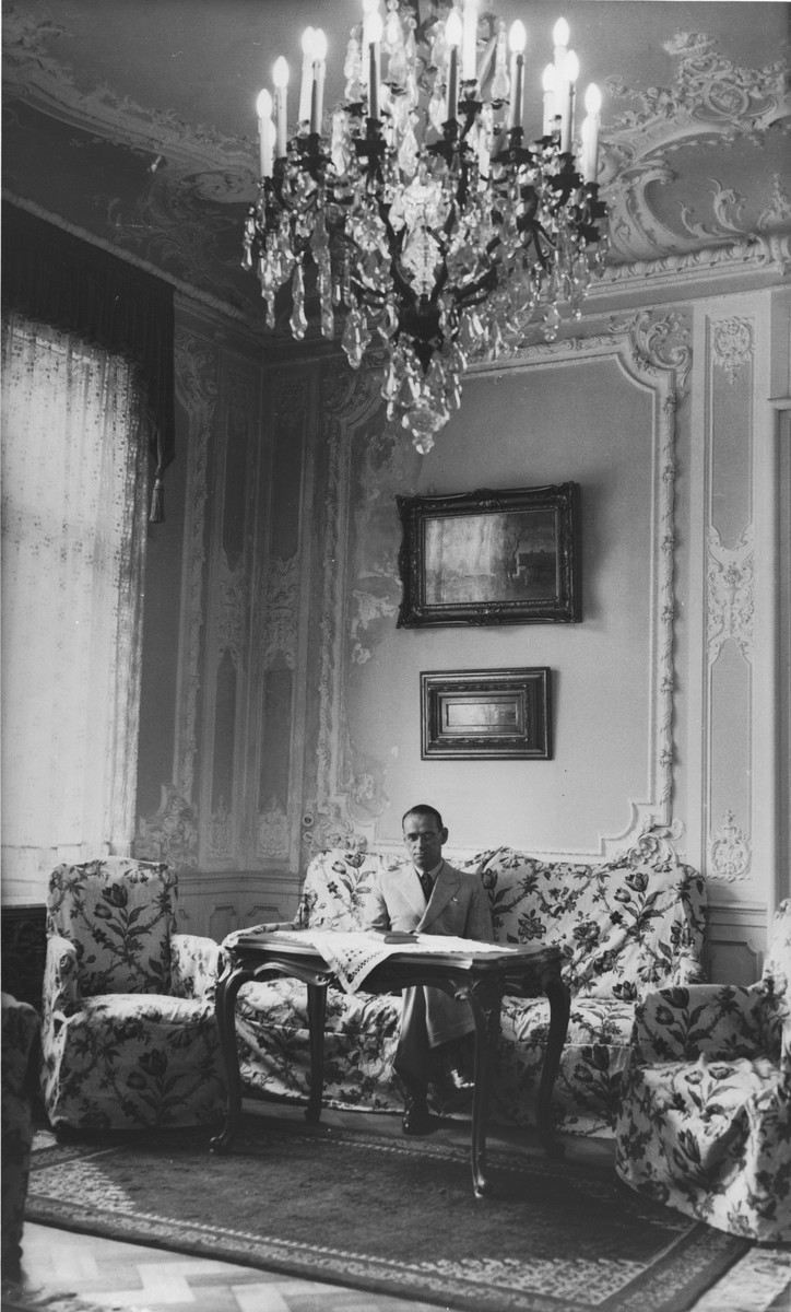 Consul Charles (Carl) Lutz sitting on a sofa in his office which was located in the American embassy in Budapest.