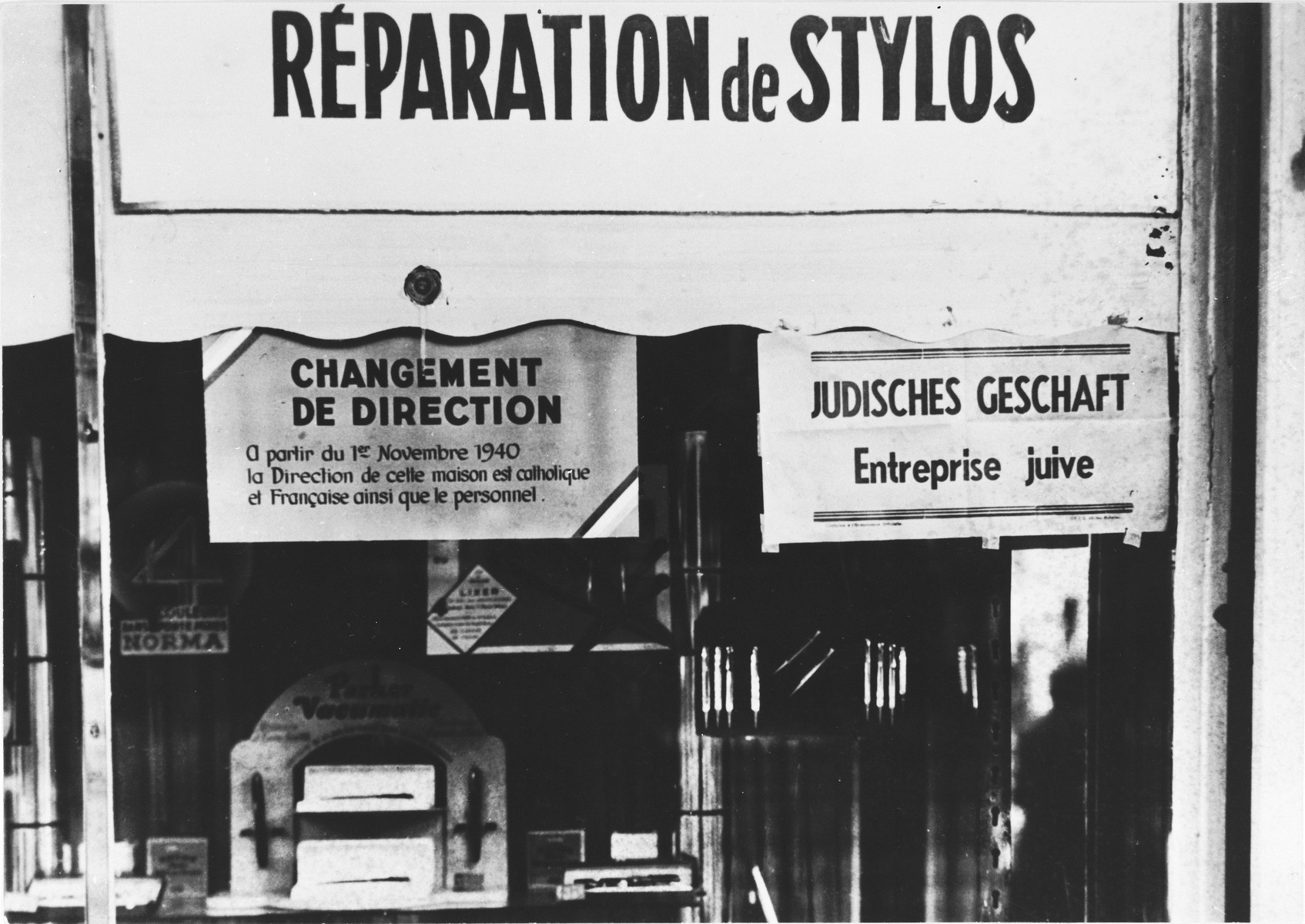 "A sign in German and French posted on a shop window  reads ""Jewish business.""  A second sign posted at the left indicates that the shop is under new management."