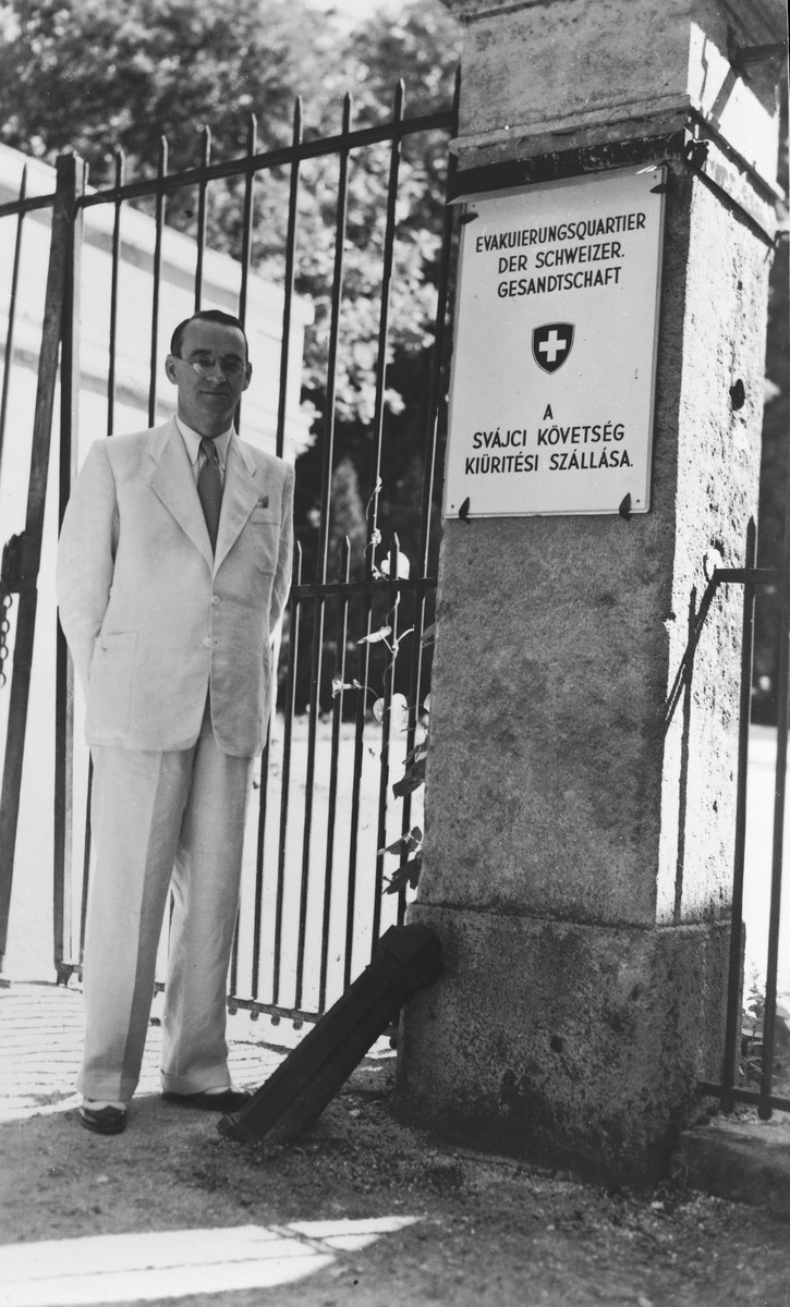 "Consul Charles (Carl) Lutz poses at the gate of the ""evacuation quarters"" of the Swiss legation in  Bicske, about half an hour from Budapest."