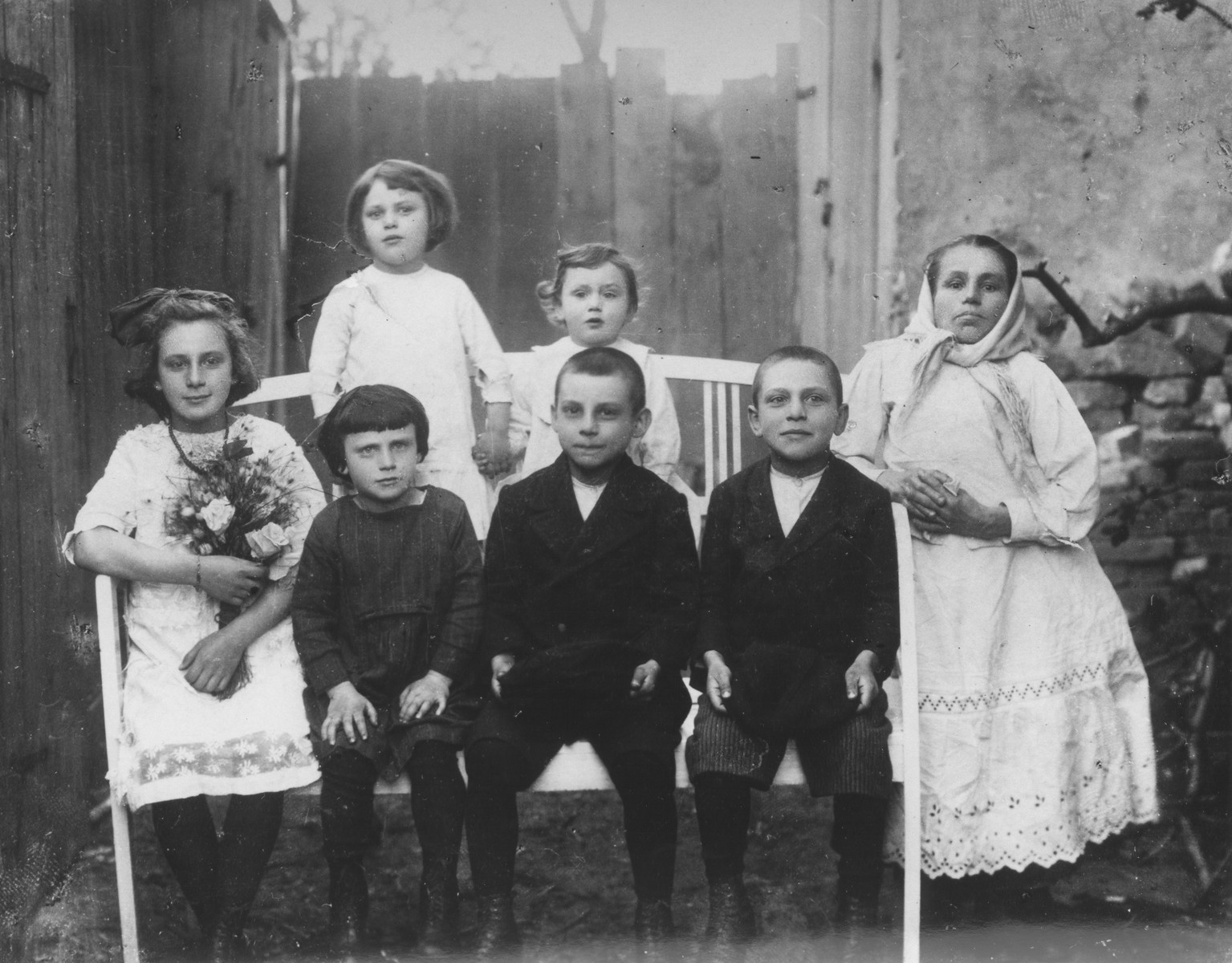 Portrait of the Stapler family outside their home in Chrzanow.  Pictured from left to right are Blimcia, Nachcia, Shlamek, and Heshek.  Top row, Goldzia and Vrumek.