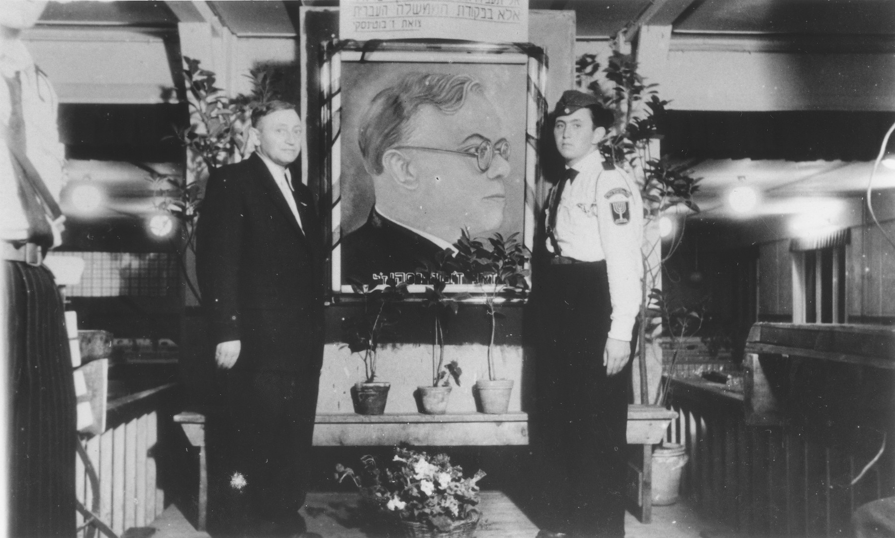 Yeshayahu Zycer and his father Ephraim pose on either side of a portrait of Zev Jabotinsky, founder of the Betar Zionist youth movement.