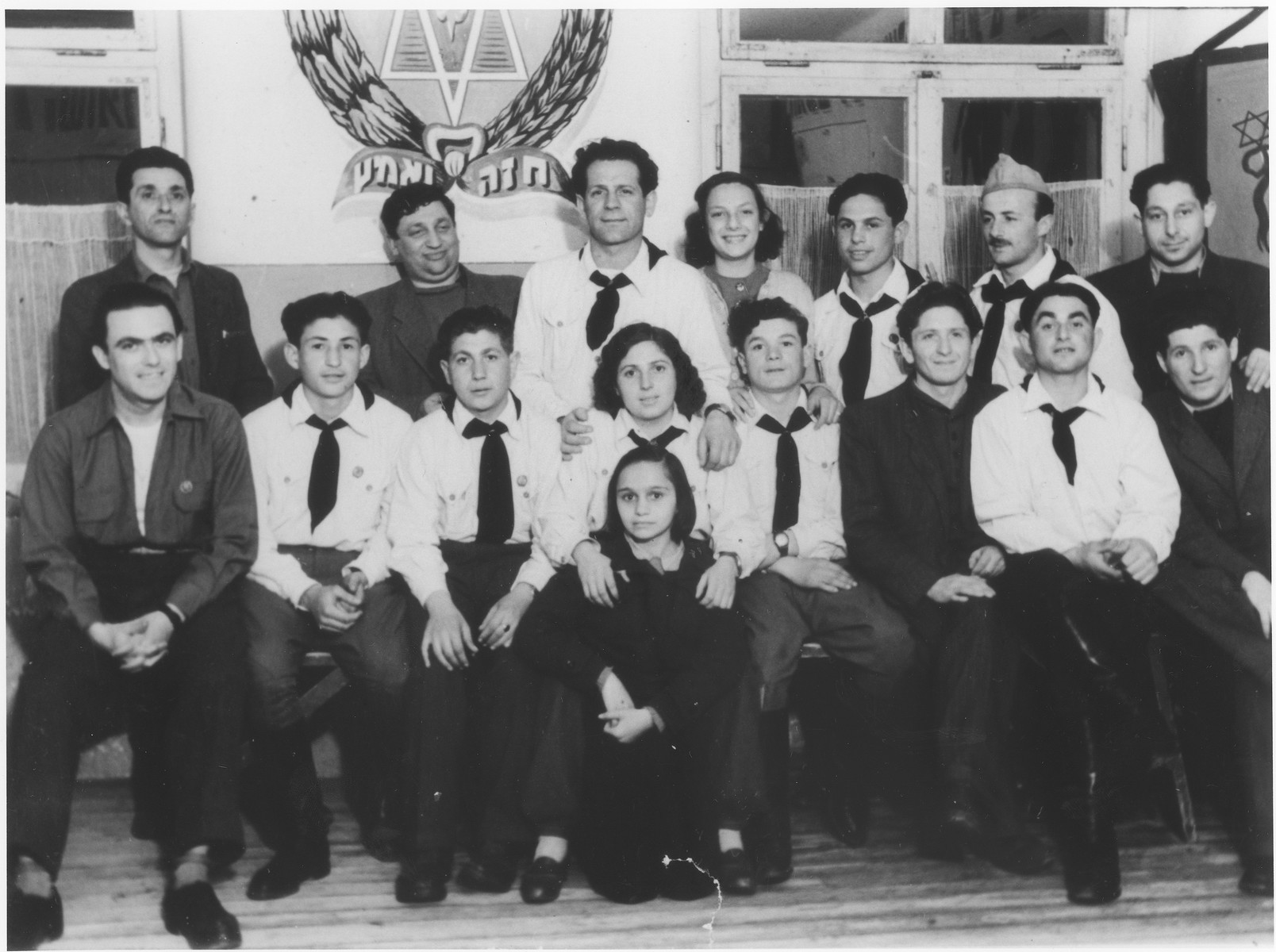 """Group portrait of Jewish scouts in the Wetzlar displaced persons camp.    On the wall is the scout emblem with the Hebrew motto, """"Be strong and brave""""."""