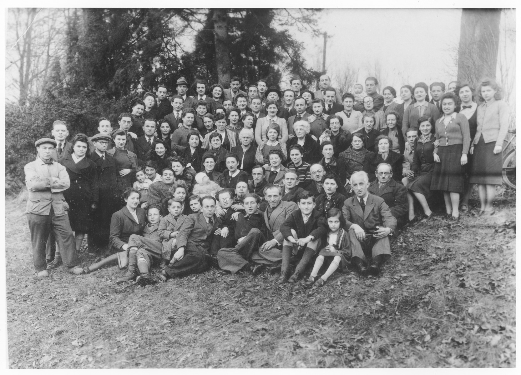 Group portrait of German Jewish refugees living in Belgium who were forcibly resettled to Bilzen after the German invasion in anticipation of their being deported back to Germany.  Among those pictured are Gisele Soldinger (second from the right), Ida Soldinger (standing on the left), Hinda Rose Soldinger (fourth row from the front, third from the right) and Edgar David Soldinger (top row, center).     Also pictured is Mendel Szydlow standing in the last row, 8th person from the right holding his infant son Werner. His wife Berta Szydlow- Sieradzki is the 2nd person to the right of him. Mendel was deported on transport X and murdered in Auschwitz. His wife and son survived the war in hiding.  Also pictured are  Menasche Steinhardt, his wife Eidla Edith Steinhardt-Safier and their son Harry Henri Steinhardt. Menasche is standing on the second row standing, second from the left, only his head visible behand the person with the darker cap. His wife with their son on her lap is sitting two persons to his right.