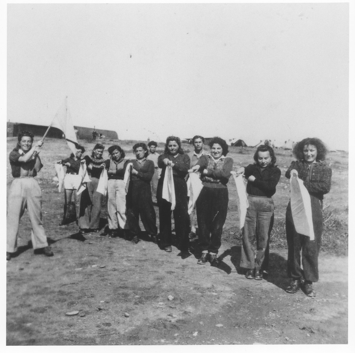 Young Jewish women who have been interned in a detention camp on Cyprus, are instructed in the use signal flags as part of their paramilitary training.  Among those pictured is Pnina Halpern (at the far right).