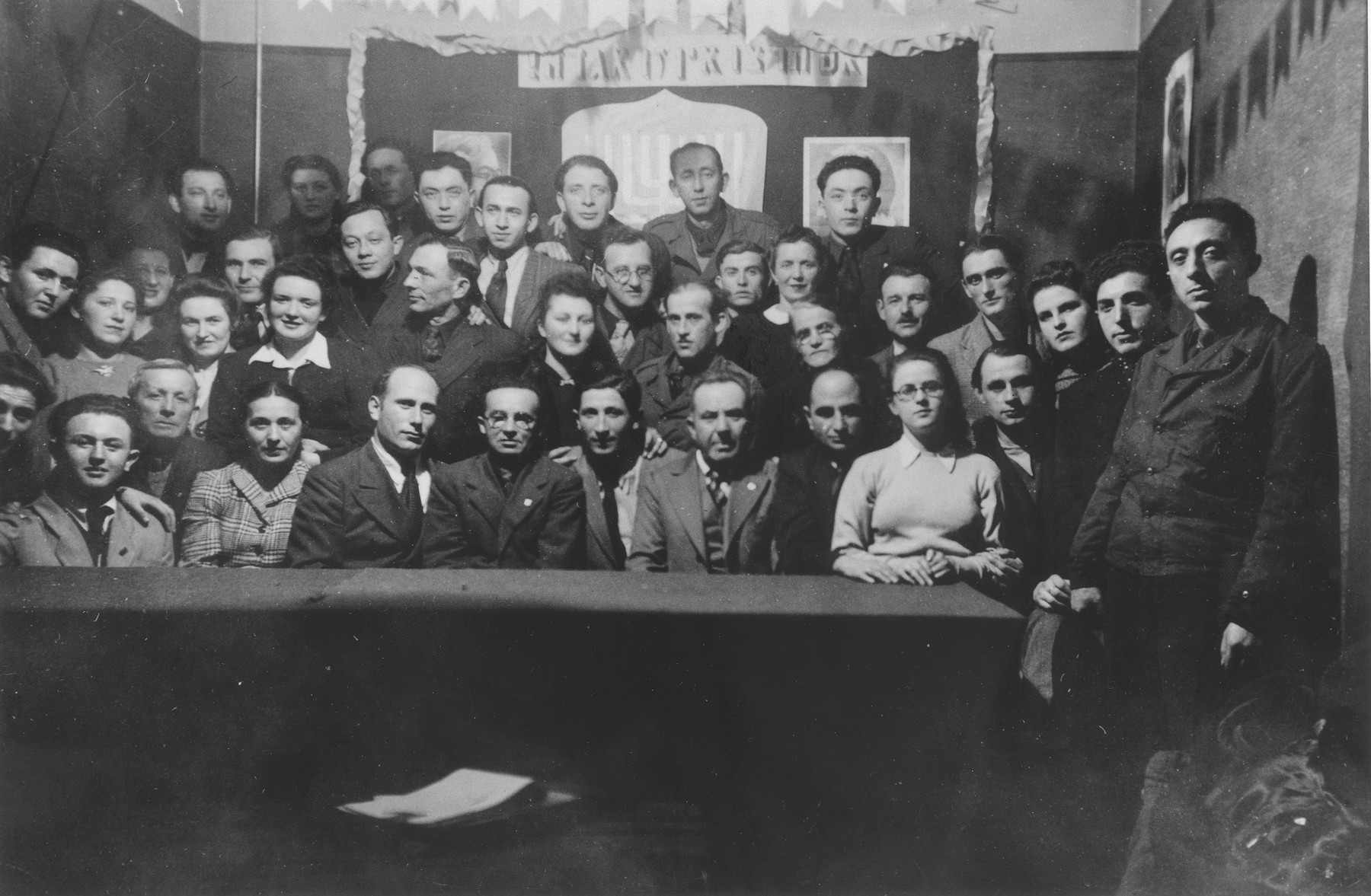 """Group portrait of members of the Betar revisionist Zionist youth movement in the Schlachtensee displaced persons camp.    The Hebrew banner on the wall is a quote from Herzl, """"If you wish it; it is no dream."""""""