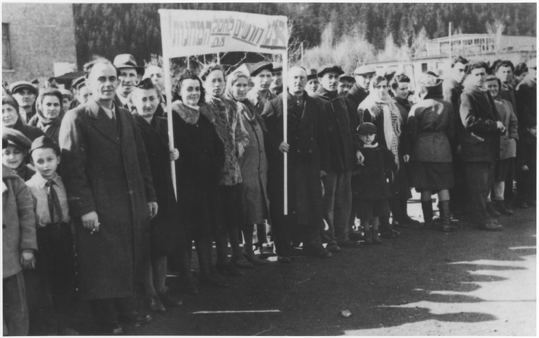 "Jewish DPs participate in a political demonstration at the Wetzlar displaced persons camp demanding the closing of the DP camps.    The Yiddish banner reads ""We demand the eradication of the [DP] camps."""