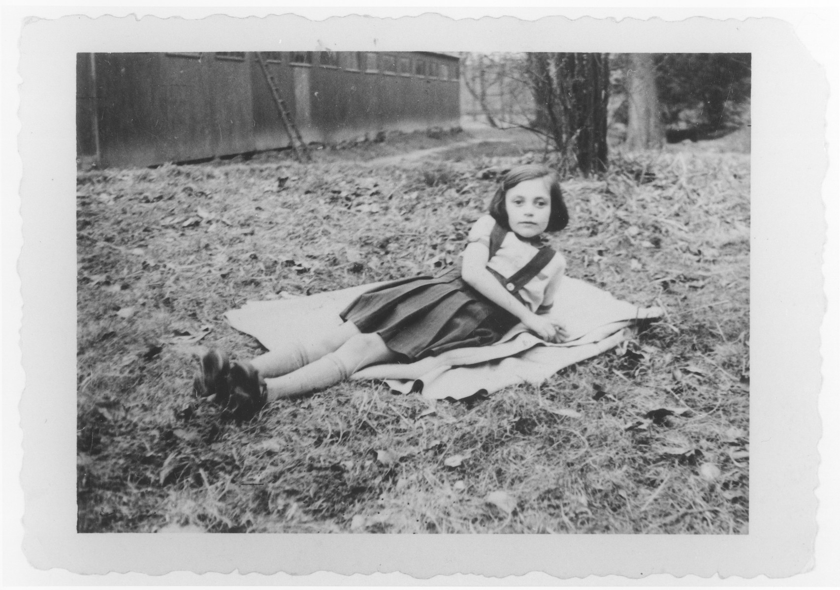 Gisela Soldinger rests on the grass in Bilzen where her family was forced to live in anticipation of deportation back to Germany.