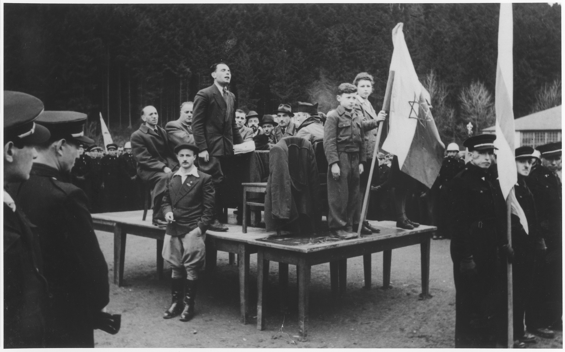 A Zionist leader delivers a speech from a makeshift podium that is ringed by uniformed Jewish police at a political demonstration in the Wetzlar displaced persons camp.