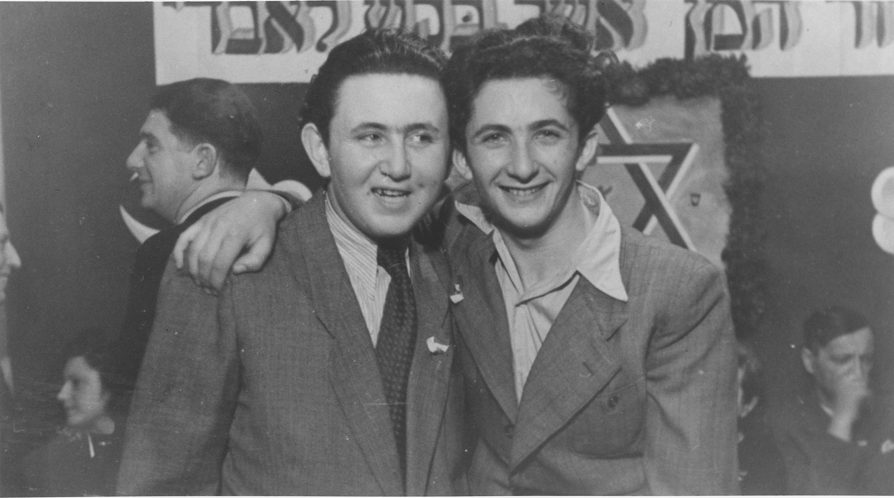 "Two young men pose at a Purim party in the Schlachtensee displaced persons camp.  Yeshayahu Zycer (left) and Mischa Gleiberman (right) stand beneath a Hebrew banner that reads, ""Cursed be Haman who tried to kill me."" (a quotation from the Book of Esther recited on the holiday of Purim)."
