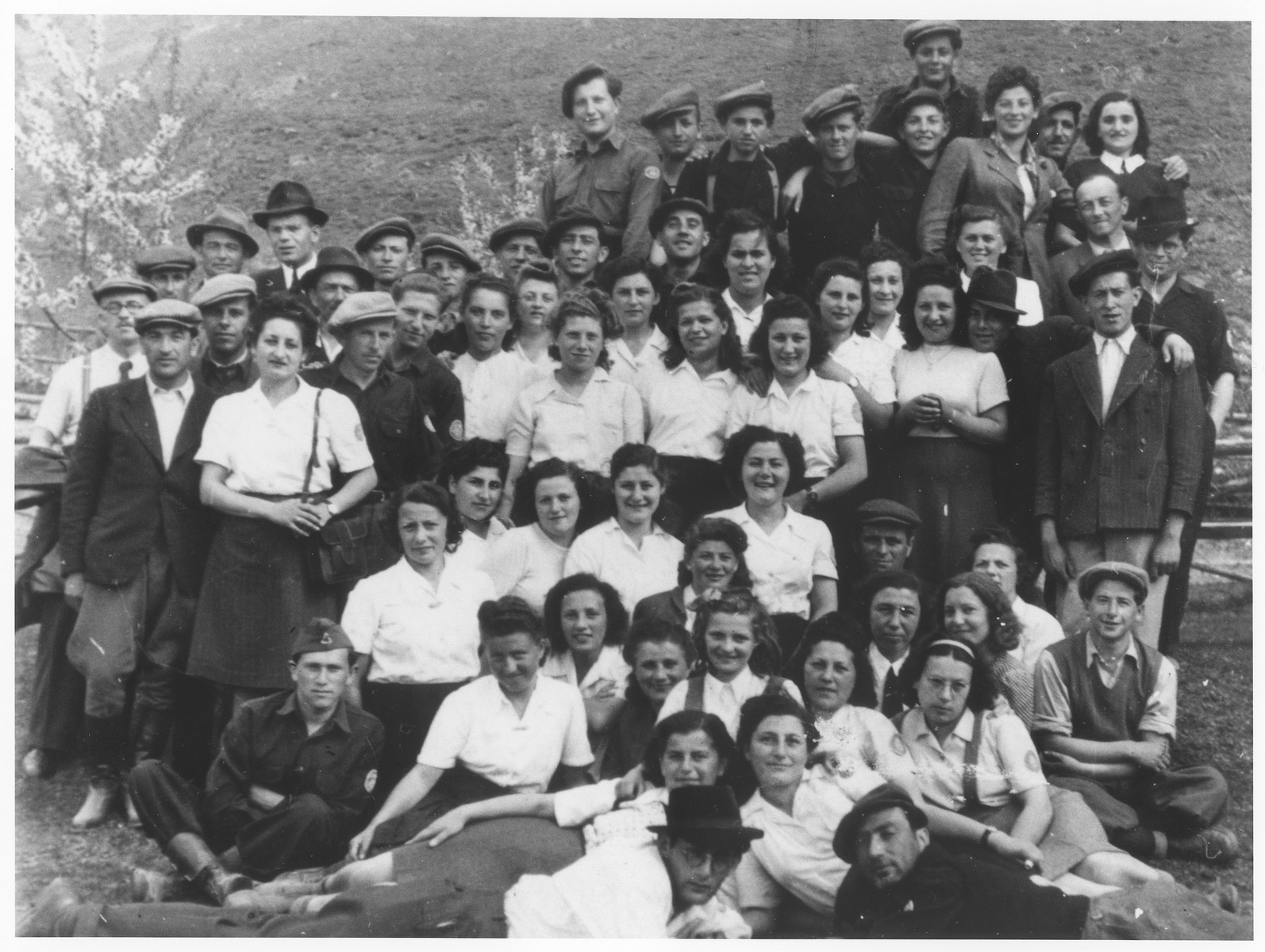 Group portrait of members of the Mizrachi religious Zionist youth movement in the Bad Gastein displaced persons camp.  Among those pictured are lying down: Schaja Klein and Meir Alexander Halpern. Directly behind Meir is Ettu Schwartz.  Maity Klein is behind her wearing a tie.  Leah Halpern is behind her to the left. In the first standing row, Moshe Weinstein is third from the left and to his left is Naftali Benhaim.  Standing in that row behind Leah is Pnina Halpern.  Also pictured are Israel Klein, Rifka Klein, , and Henryk Klein.