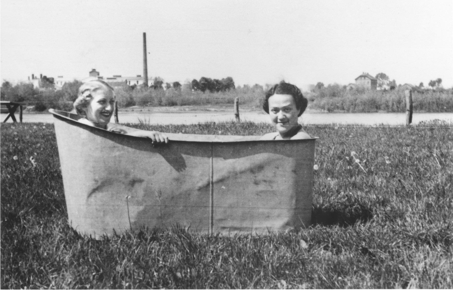 Lotte Gottfried (left) and Roszi Kaufmann sit in a tub along the banks of the Prut River in Czernowitz.