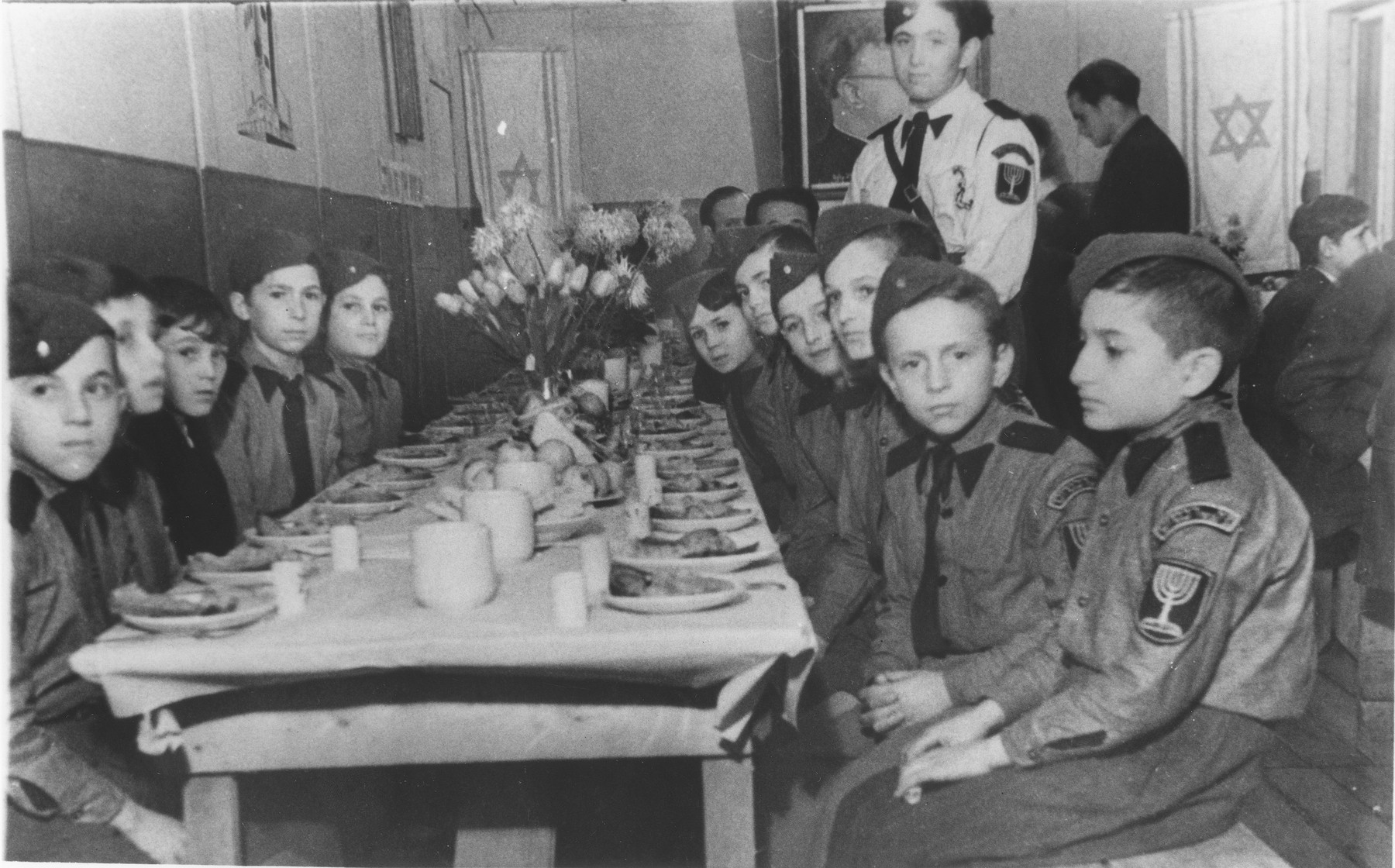 Young boys dressed in Betar Zionist youth uniforms, are about to eat a meal in the dining room of the Schlachtensee displaced persons camp.  Yeshayhu Zycer is pictured standing in front of the portrait of Zev Jabotinsky, founder of the Betar Zionist youth movement.