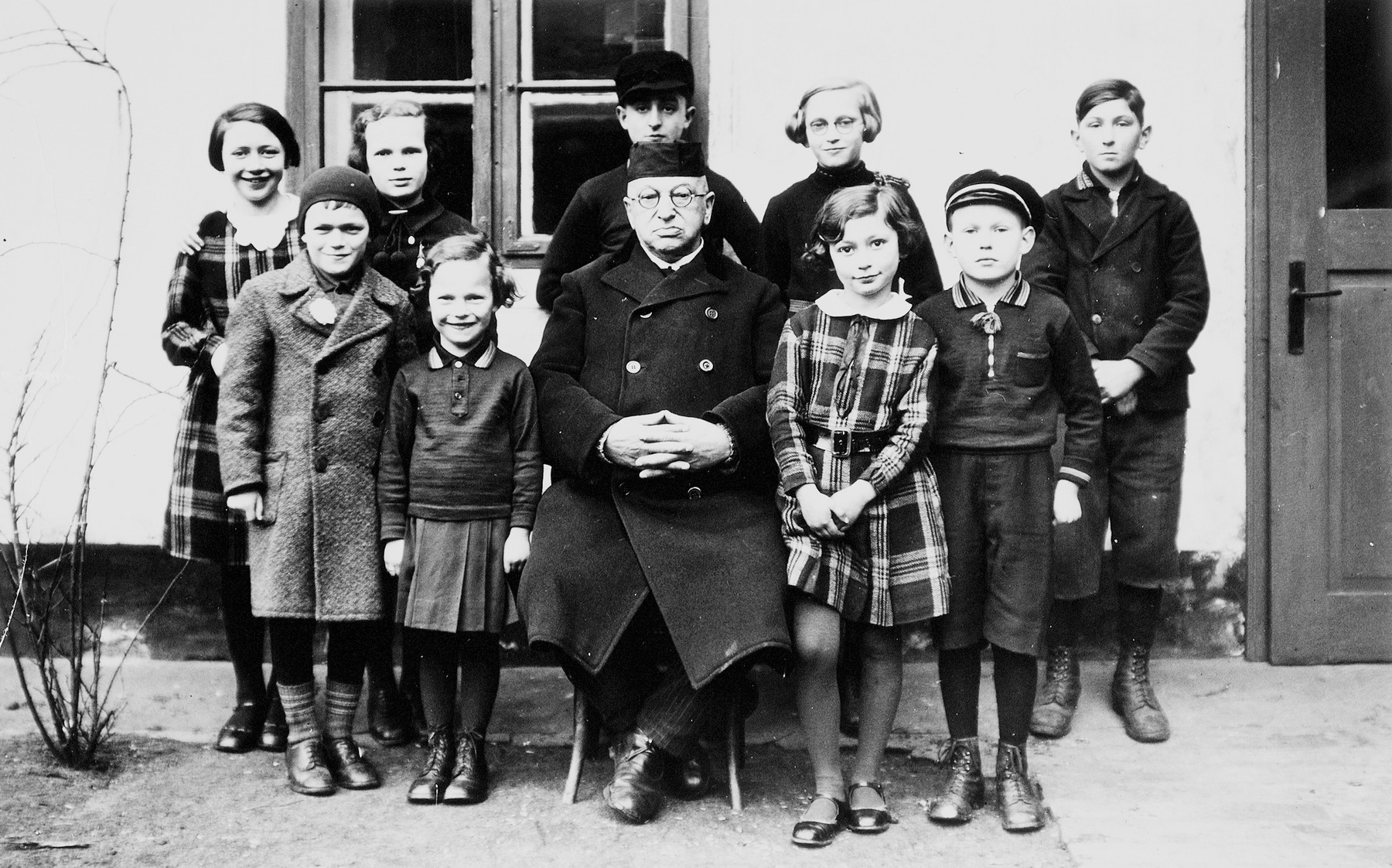 Herbert and Ruth Karliner (front row, left) pose with a group of children and an unidentified man outside a building in Peiskretscham, Germany.