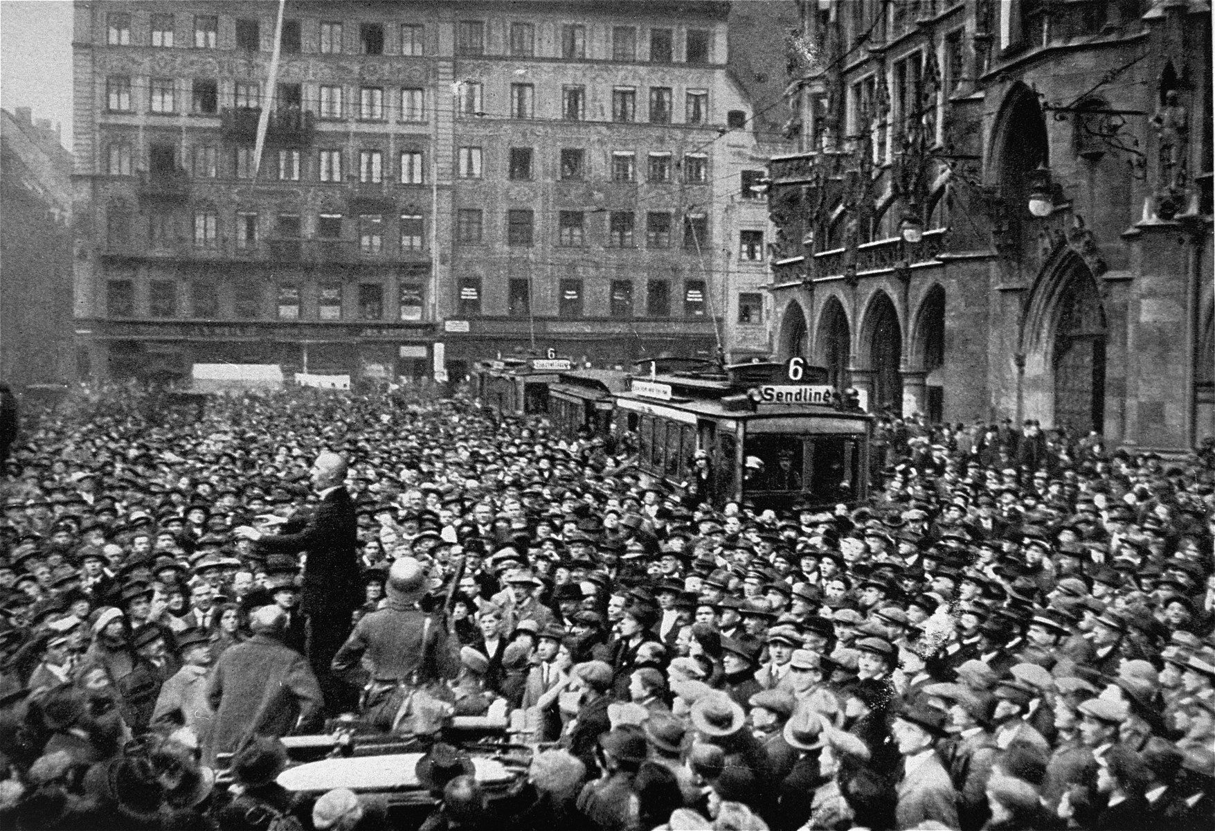 "A large crowd gathers in front of the Rathaus to hear the exhortations of a Nazi orator [possibly Julius Streicher] during the ""Beer Hall Putsch."""