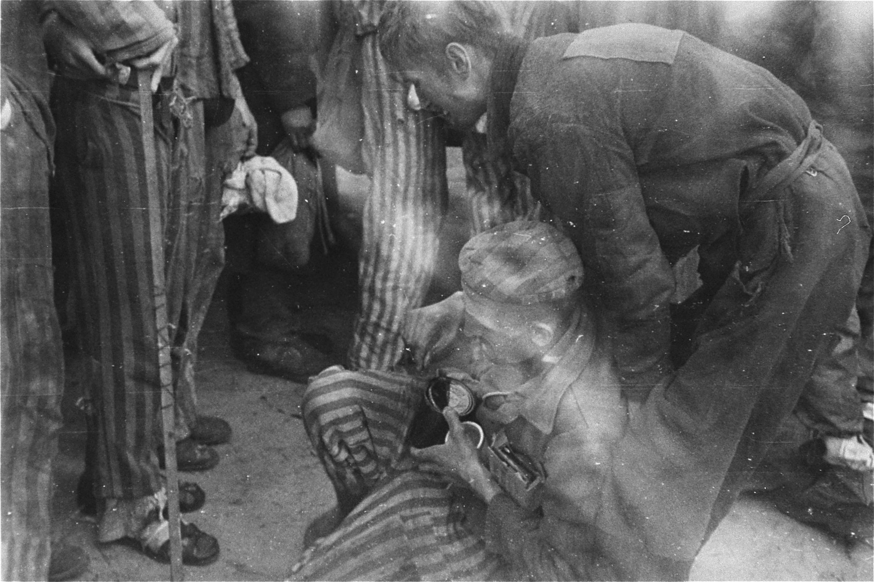 A survivor carrying rations given to him by an American soldier is evacuated from the Woebbelin concentration camp to a field hospital where he will be given medical attention.