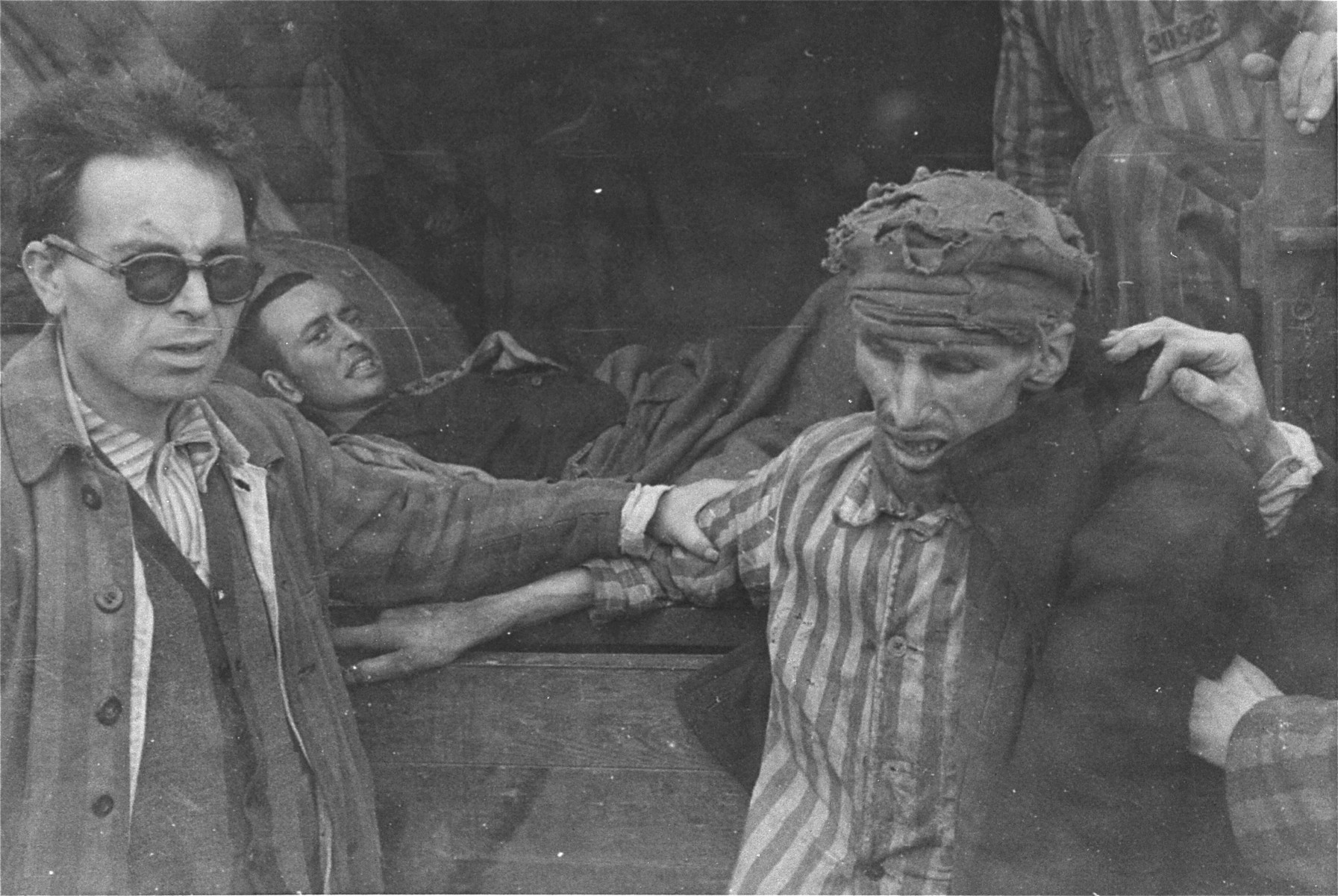 """David Rousset, a former correspondent for """"Time"""" and """"Life"""" magazines, helps to evacuate starved prisoners from the newly liberated Woebbelin concentration camp."""