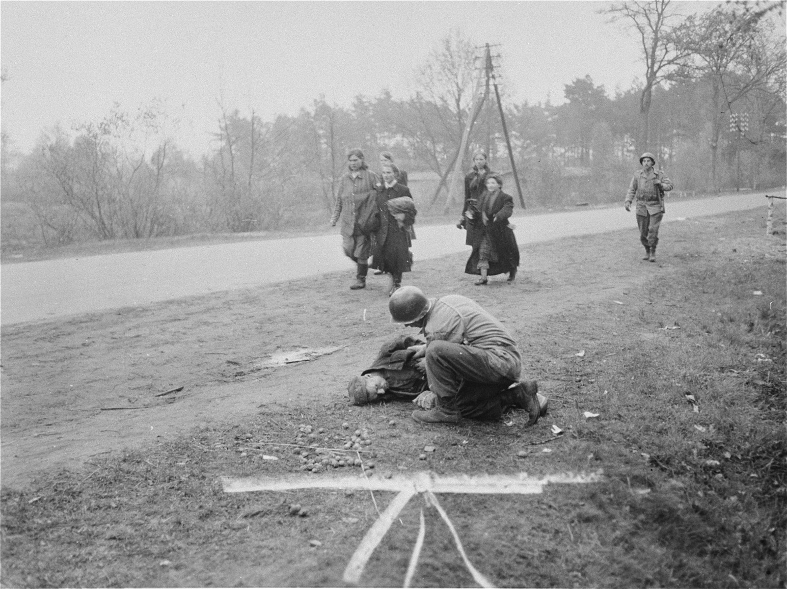 A Polish survivor from the Woebbelin concentration camp, drops dead from malnutrition at the side of the road shortly after his liberation.  A U.S. soldier tries in vain to administer aid to the man, while in the background liberated Polish women pass by carrying shoes confiscated from local German women.