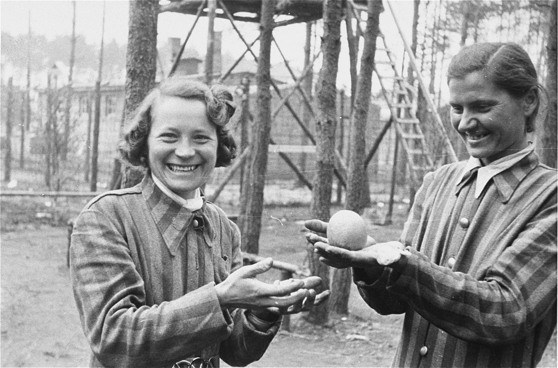 Women survivors in the womens' camp in Woebbelin hold an orange given to them by an American soldier.