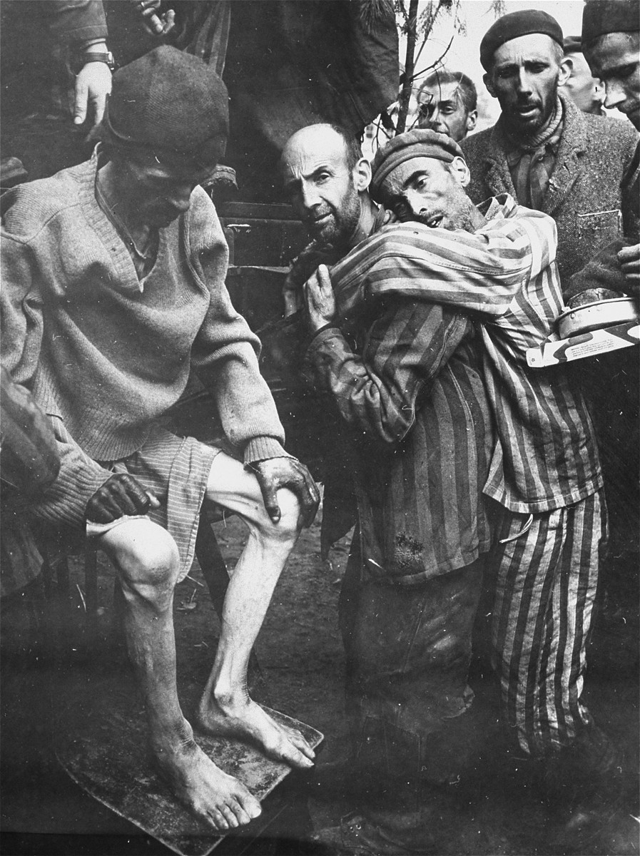 "The evacuation of survivors from the Woebbelin concentration camp to an American field hospital.  Among those pictured, center, carrying a fellow survivor is Aliende, a political prisoner.   The original caption reads ""This is one of a series of pictures taken at German Concentration Camp in Woebling, Germany after its capture by troops of the 82nd Airborn Division, 9th Army.  These former prisoners of the Germans are being taken to a hospital for much needed medical attention after being nearly starved to death."" ----------------- The original Signal Corps caption reads, ""NEW NAZI HORROR CAMP DISCOVERED.  One of the worst Nazi concentration camps uncovered by Allied troops was liberated at Wobbelin, Germany, a small town five miles north of Ludwigslust and 90 miles northwest of Berlin.  Soldiers of three Allied units -- the 82nd U.S. Airborne Division, the Eighth Infantry Division of the Ninth U.S. Army and airborne troops of the Second British Army -- entered the camp and found sick, starving inmates barely surviving under indescribable conditions of filth and squalor.  They found hundreds of dead prisoners in one of the buildings while outside, in a yard, hundreds more  were found hastily buried in huge pits.  One mass grave contained 300 emaciated, disfigured corpses.  The dead included Poles, Russians, Frenchmen, Belgians, Dutchmen and Germans, all of whom had been working as slave laborers for the Nazis.  It is estimated that at least 150 of the original 4,000 prisoners succumbed daily, mostly from starvation and savage treatment at the hands of Nazi SS troops who operated the camp.   Some of the bodies found were burned almost beyond recognition and systematic torture of the inmates was revealed by the  physical condition of most of the survivors.  Military Government officers immediately ordered leading citizens of nearby Ludwigslust and other towns to march through the camp and witness the atrocities committed by representatives of the German Government.  Most of the civilians disclaimed any knowledge of the camp's existence despite the fact that many of the prisoners worked in the area.  The local residents later were made to exhume the bodies from the mass graves at the camp and provide decent, respectable interment of all dead prisoners.  Two hundred were buried in the public square of Ludwigslust May 7, 1945, and an equal number were buried in the garden of the highest Nazi official of Hagenow.  Eighty more were laid to rest in the town of Schwerin.  BIPPA                                                         EA 66641  THIS PHOTO SHOWS:  Sick and half-starved prisoners are removed from  tHE Wobbelin camp for treatment at a hospital.  U.S. Signal Corps Photo ETO-HQ-45383 SERVICED BY LONDON OWI TO LIST B CERTIFIED AS PASSED BY SCHAEF CENSOR   Original caption from donated photograph reads,  ""Sick and half-starved prisoners at the concentration camp at Wobbelin, Germany, are removed for hospitalization after seizure of the area by U.S. troops.  Wobbelin was considered one of the worst of the many German concentration camps liberated by the Allies.  Hundreds of dead bodies lay near dying inmates and hundreds more were found hastily buried in huge pits.  One mass grave contained 300 emaciated, disfigured corpses, bodies of former slave laborers who succumbed to brutal treatment and starvation.  It is estimated that at least 150 of the original 4,000 prisoners died daily."""