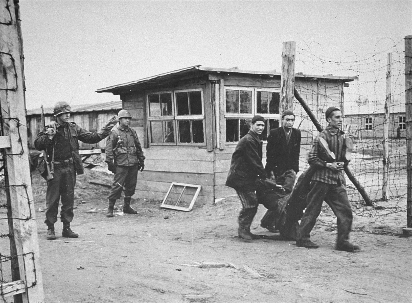 An American guard waves through the gate a group of survivors carrying a comrade who escaped from Woebbelin a few days before its liberation by the 82nd airborne division, 9th US Army.    The man dropped from starvation outside the enclosure as he tried to make his way back to a source of food.