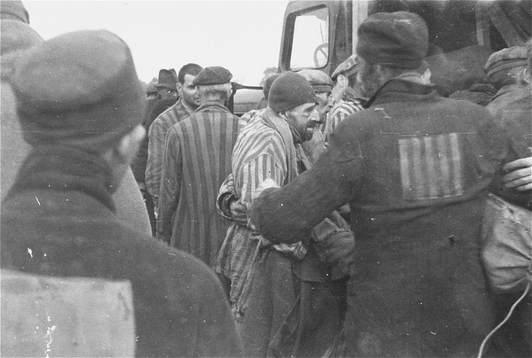 Stronger survivors help to evacuate their weaker fellows from the Woebbelin concentration camp to an Allied field hospital for medical attention.