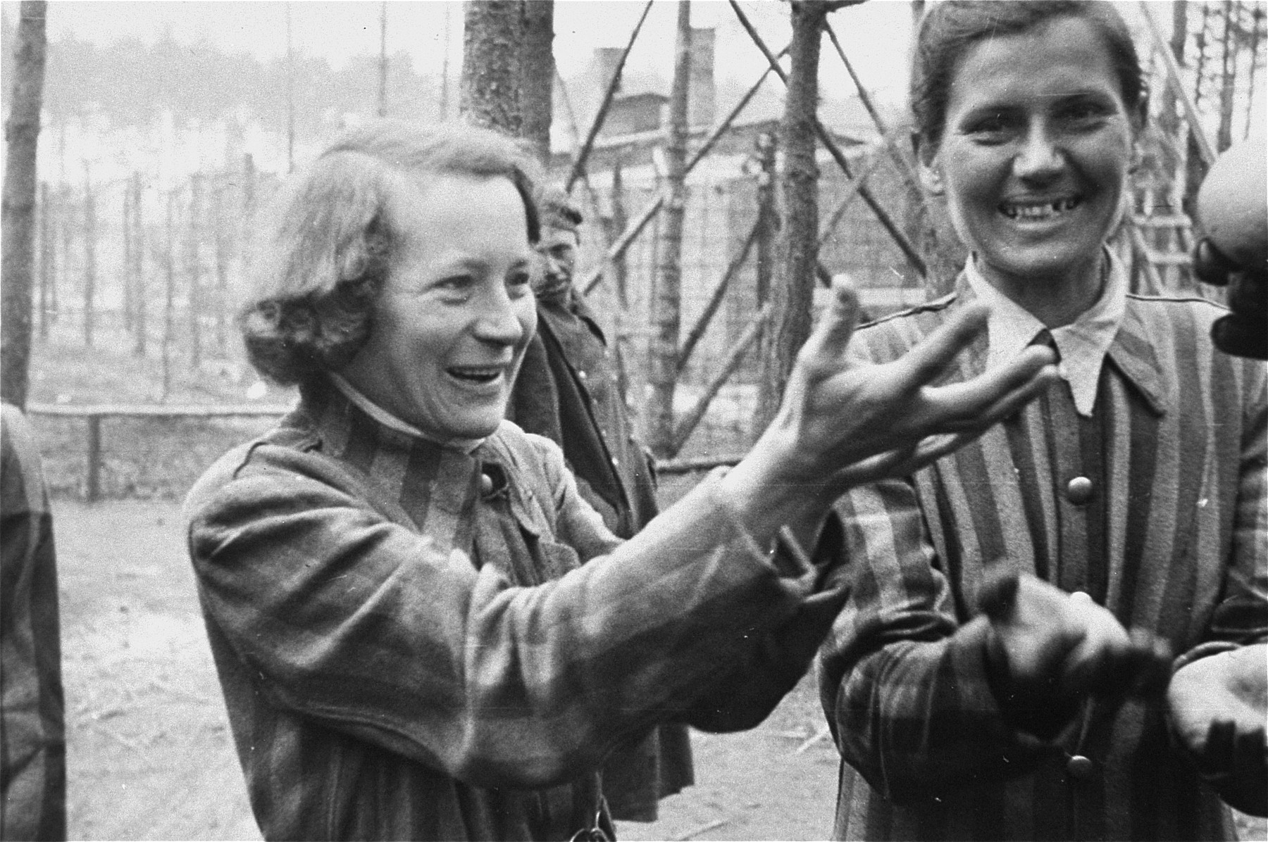 Women survivors in the Woebbelin concentration camp reach for oranges handed to them by American soldiers.