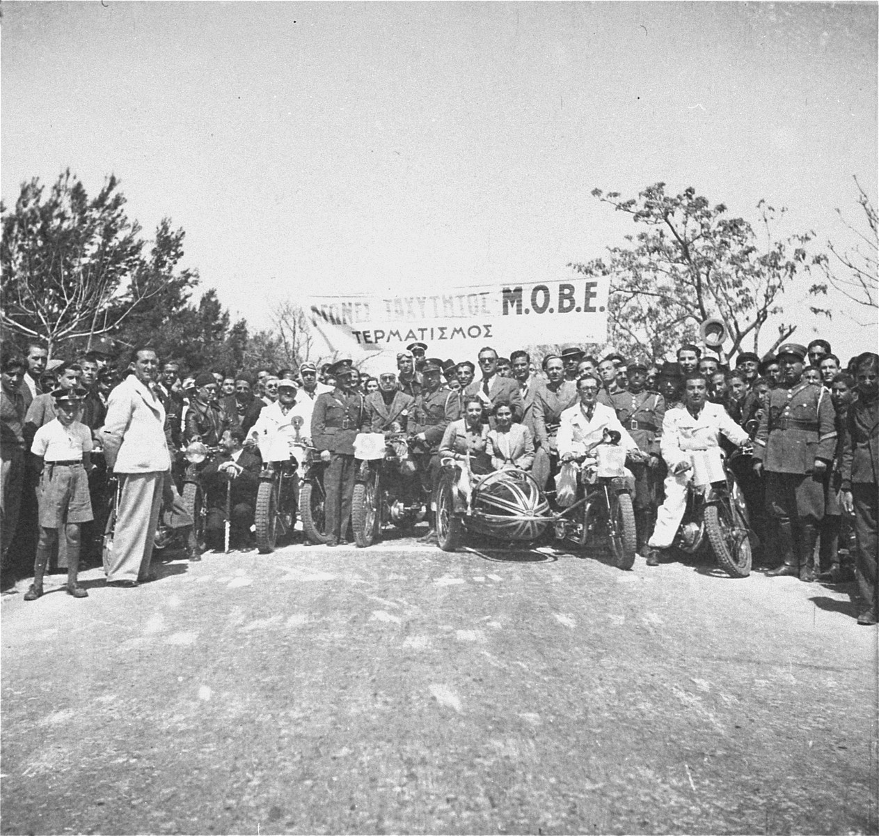 Competitors and spectators pose at the starting line of a motorcycle race in Salonika.  The donor, Leon Benveniste, is pictured on the bike at the right.