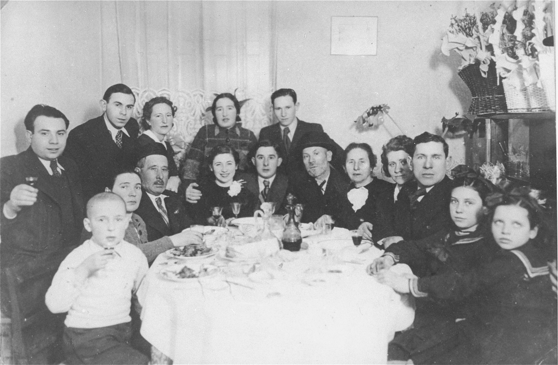 Portrait of members of the Wisgardisky family seated around a table during an engagement party for Yente Wisgardisky and Berl Berk.  Yente Wisgardisky is the aunt of the donor, Henia Lewin.  Pictured standing behind, from left to right are: Melech; Jona and Gita; unknown; and Hershel Wisgardisky.  Seated from right to left are: four members of the Apzig family (two daughters and their parents, who were all killed by the Germans); the donor's grandparents; Berl Berk; and Yente Wisgardisky.  The man seated third from the left has been tentatively identified as Josel (Josef) Berk, father of Berl Berk.