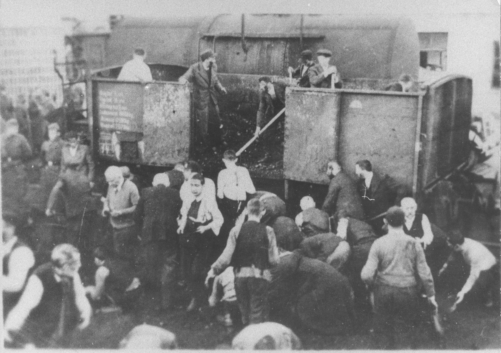 Jewish men at forced labor unload a wagon laden with coal.